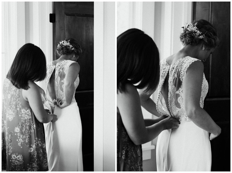 Sister helping bride get into dress at cabin wedding in Brainerd Minnesota