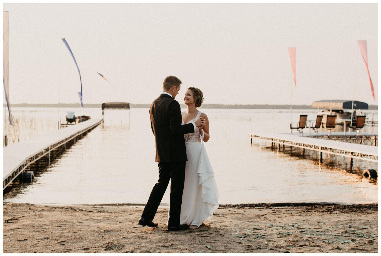 Bride and groom dancing at sunset on Lake Edward