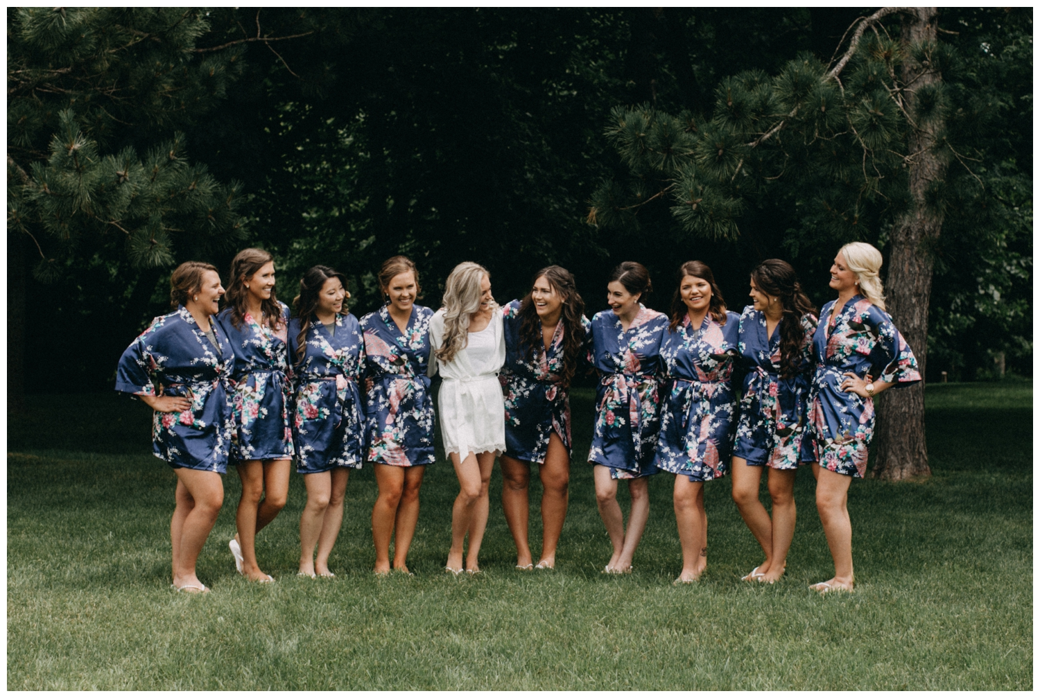 Bride poses with bridesmaids in blue floral robes at Creekside Farm wedding