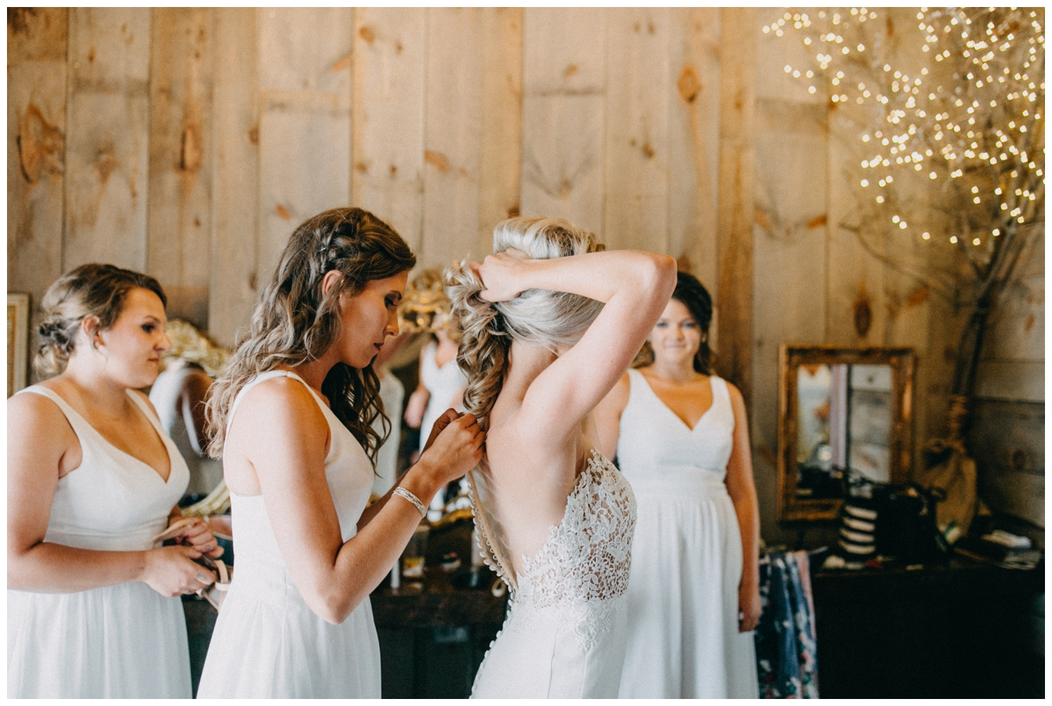Bridesmaid helping button brides wedding dress at Creekside Farm in Rush City, MN