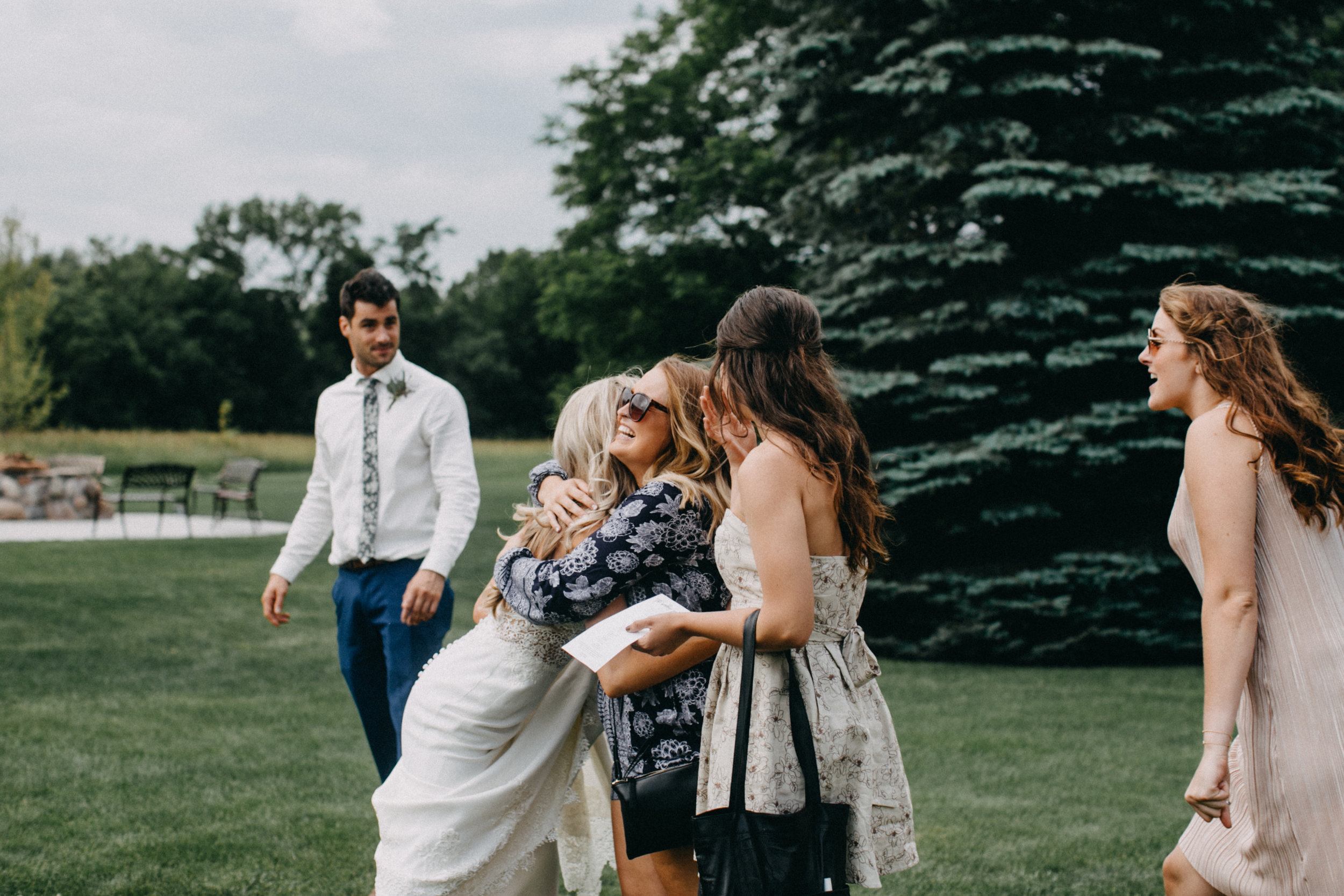 Emotional and candid moment of bride with friends during wedding reception at Creekside Farm wedding in Rush City photographed by Britt DeZeeuw