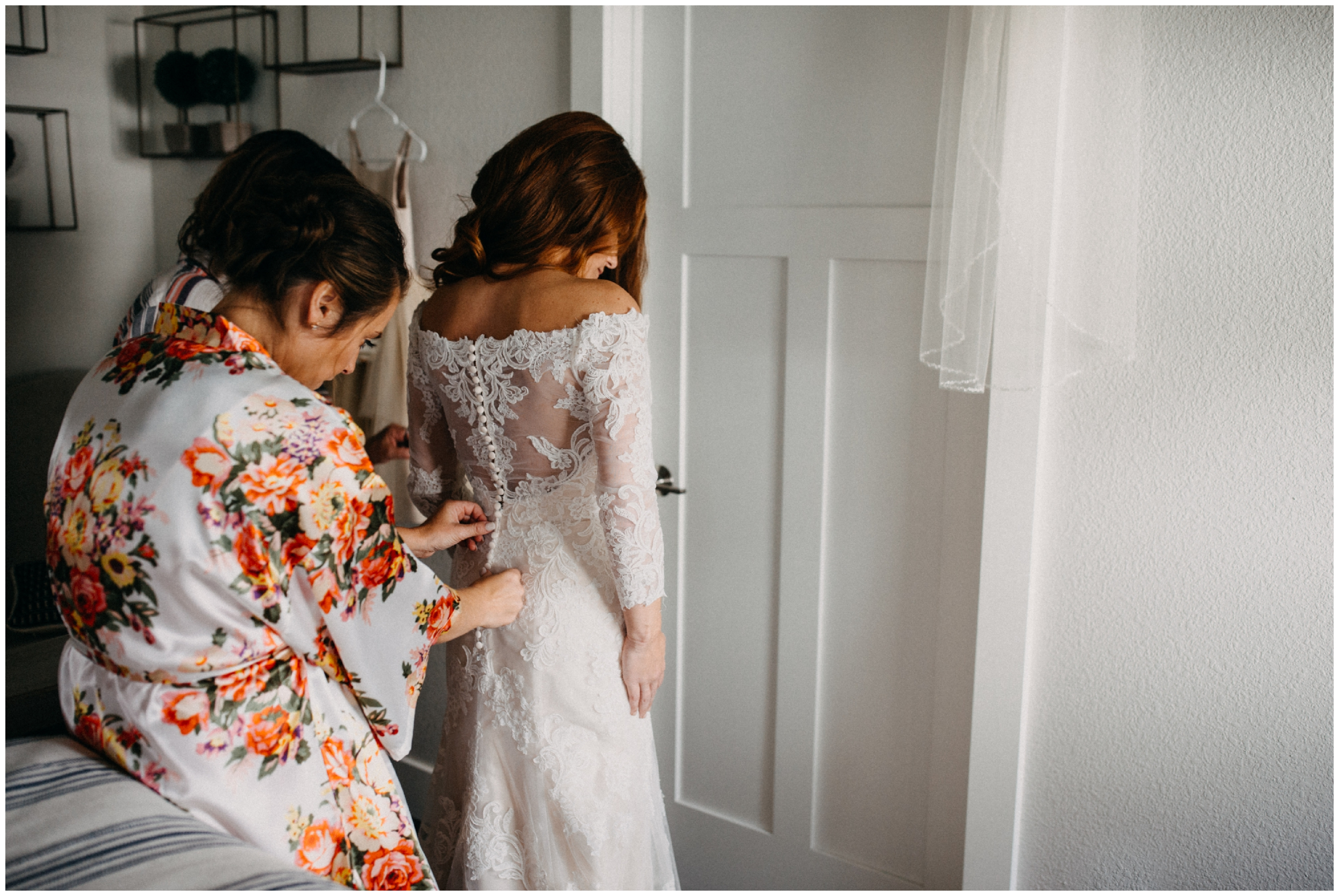 Bride getting into lace, long sleeved wedding dress at the Quarterdeck on Gull Lake