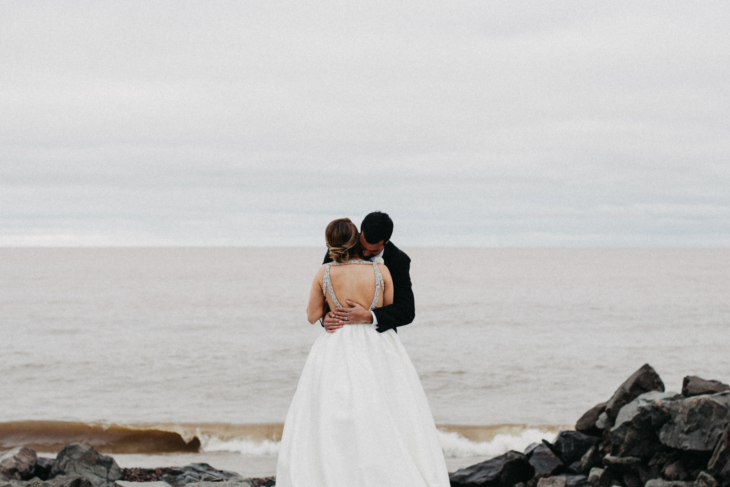 Bride and groom embracing on the north shore in Duluth Minnesota