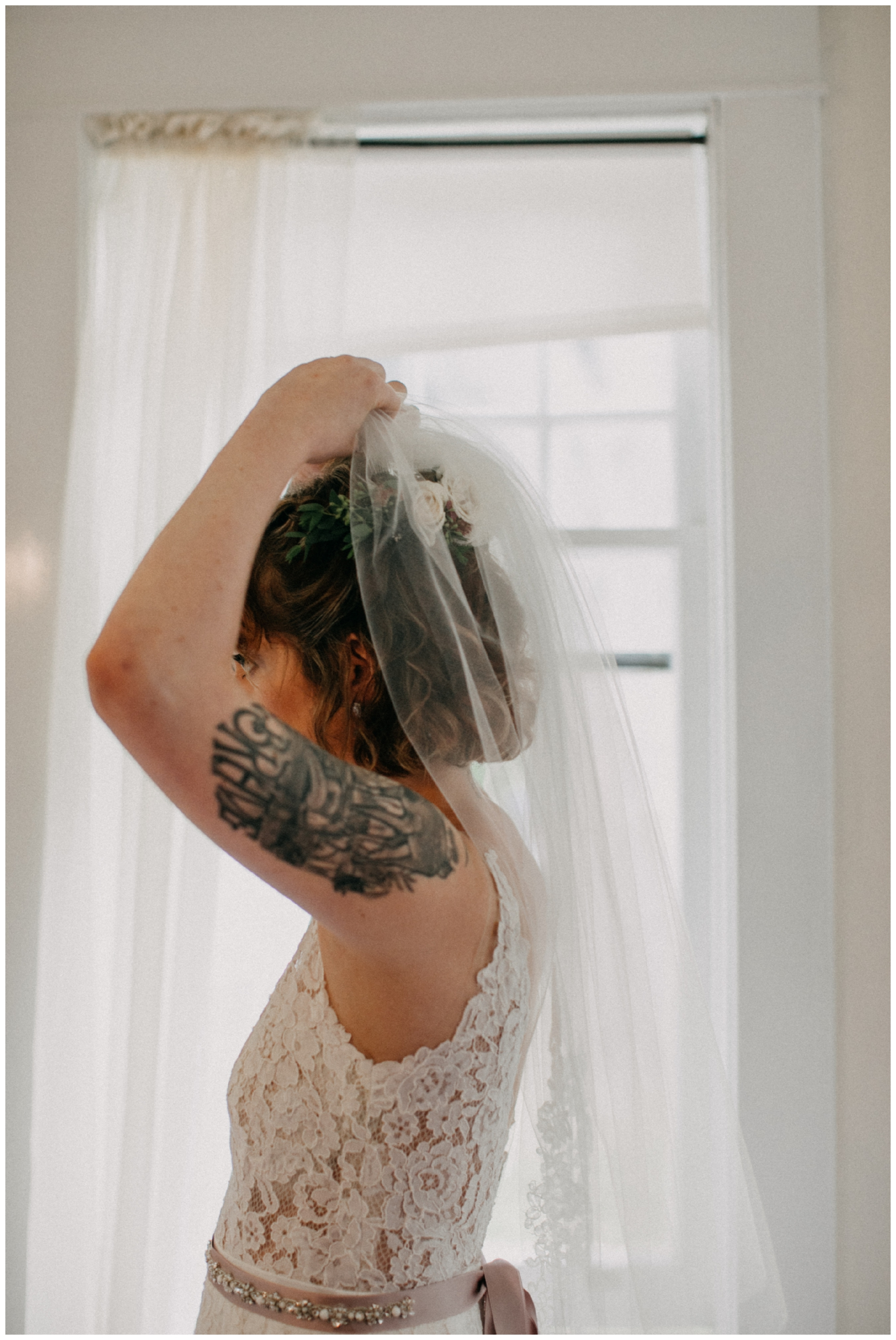 Modern and elegant bridal portrait of bride putting on veil in Duluth Minnesota