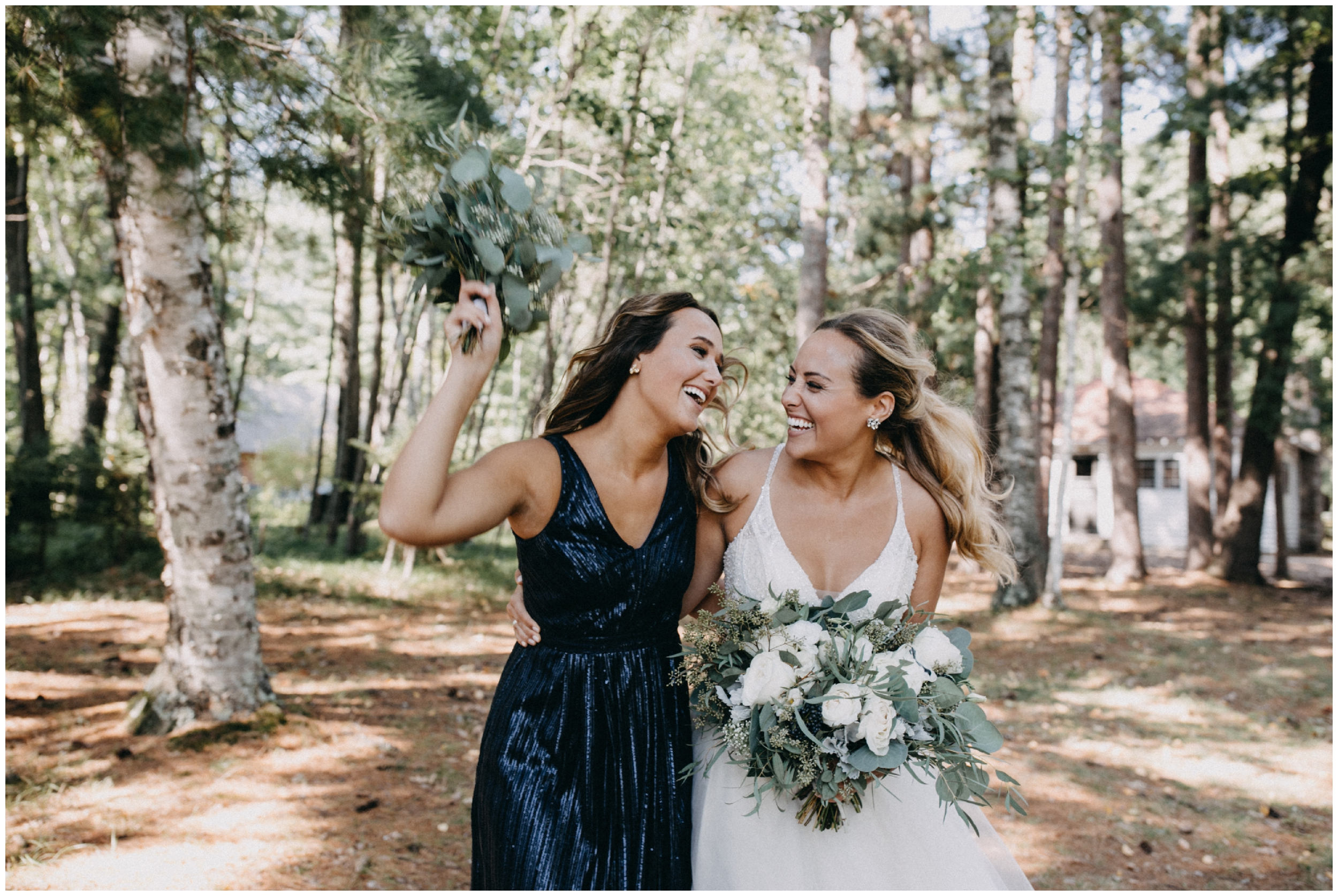 Bride and sister candidly pose at Camp Foley wedding in Pine River