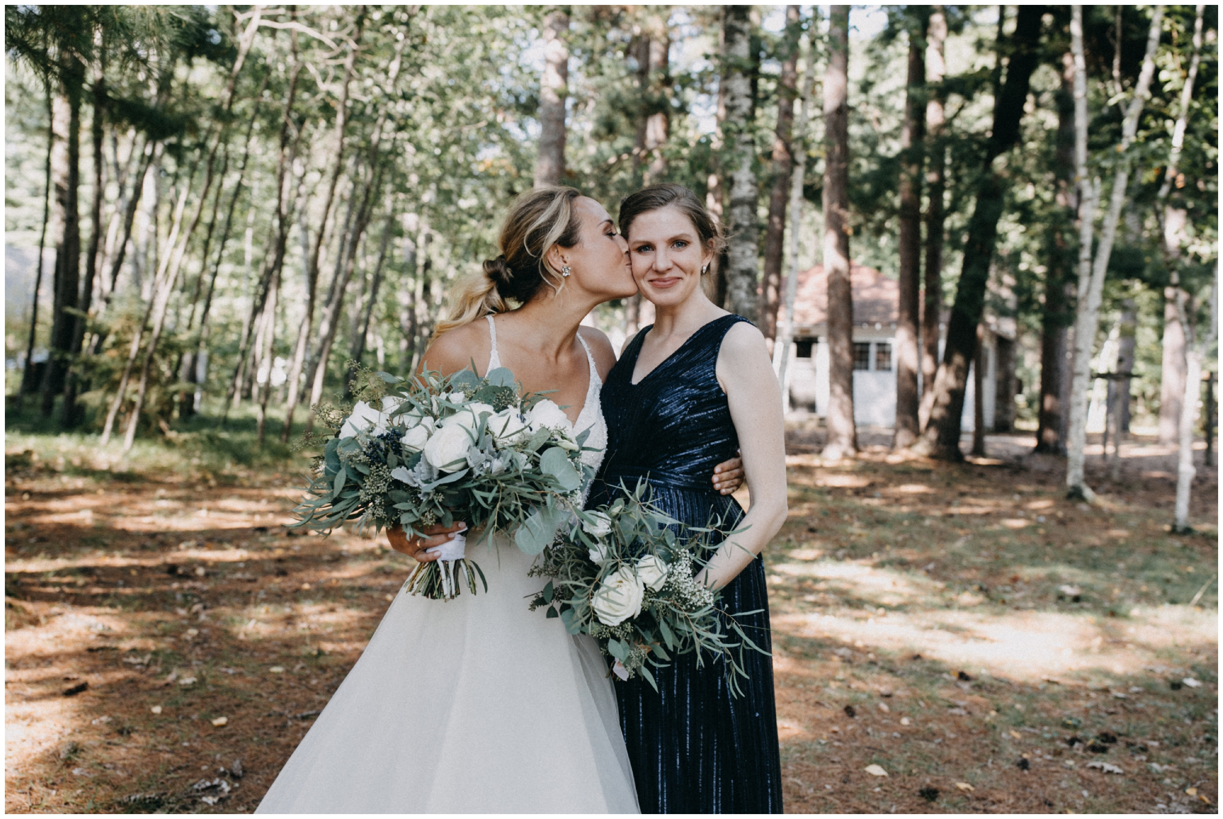 Bride posing candidly with bridesmaid at Camp Foley wedding in Pine River Minnesota
