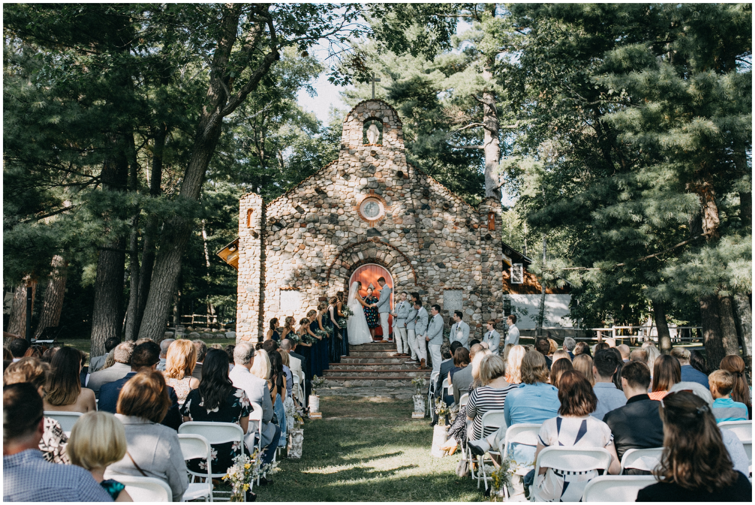Romantic stone chapel wedding ceremony in the woods at Camp Foley