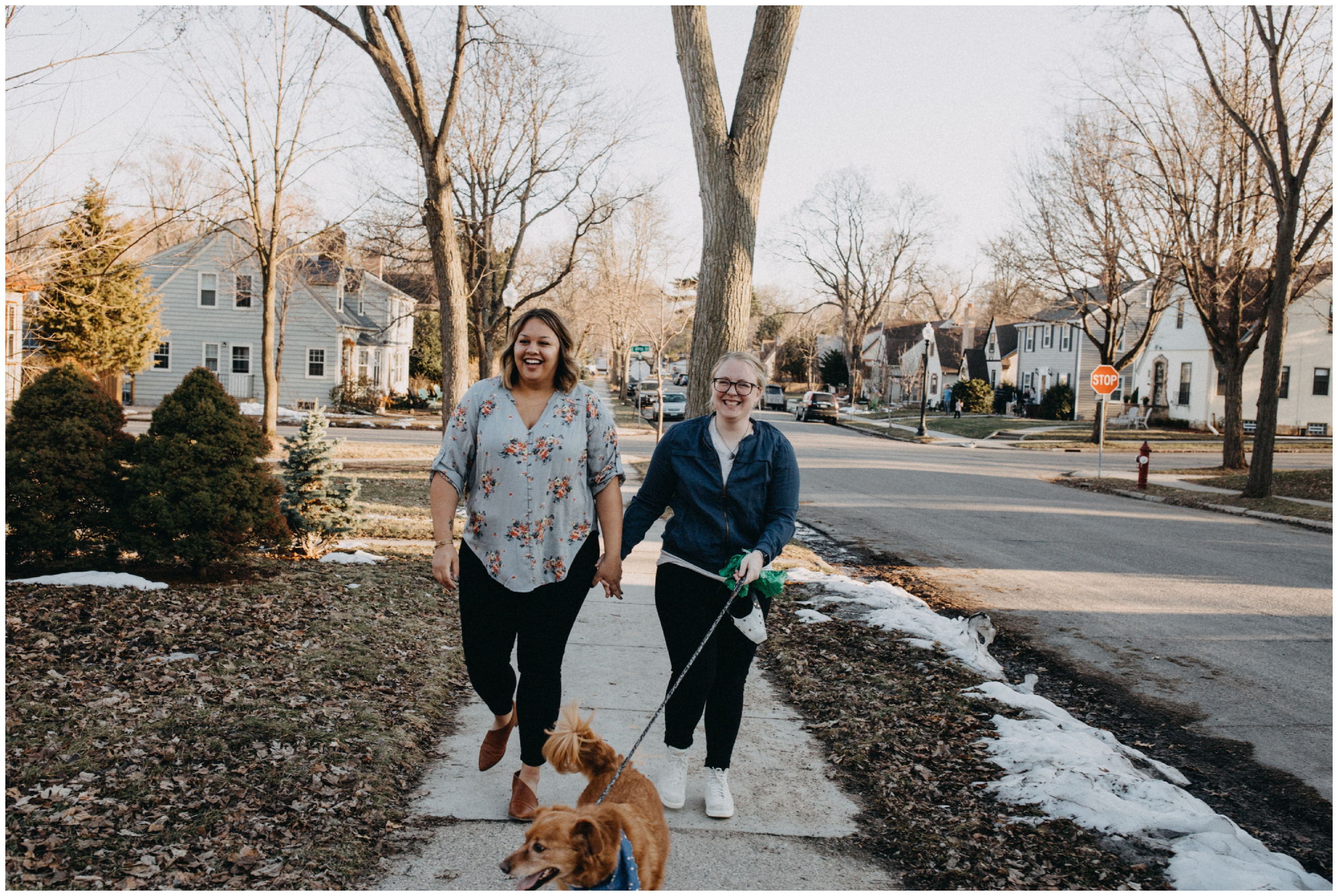 Same sex couple walking dog during Minneapolis engagement session