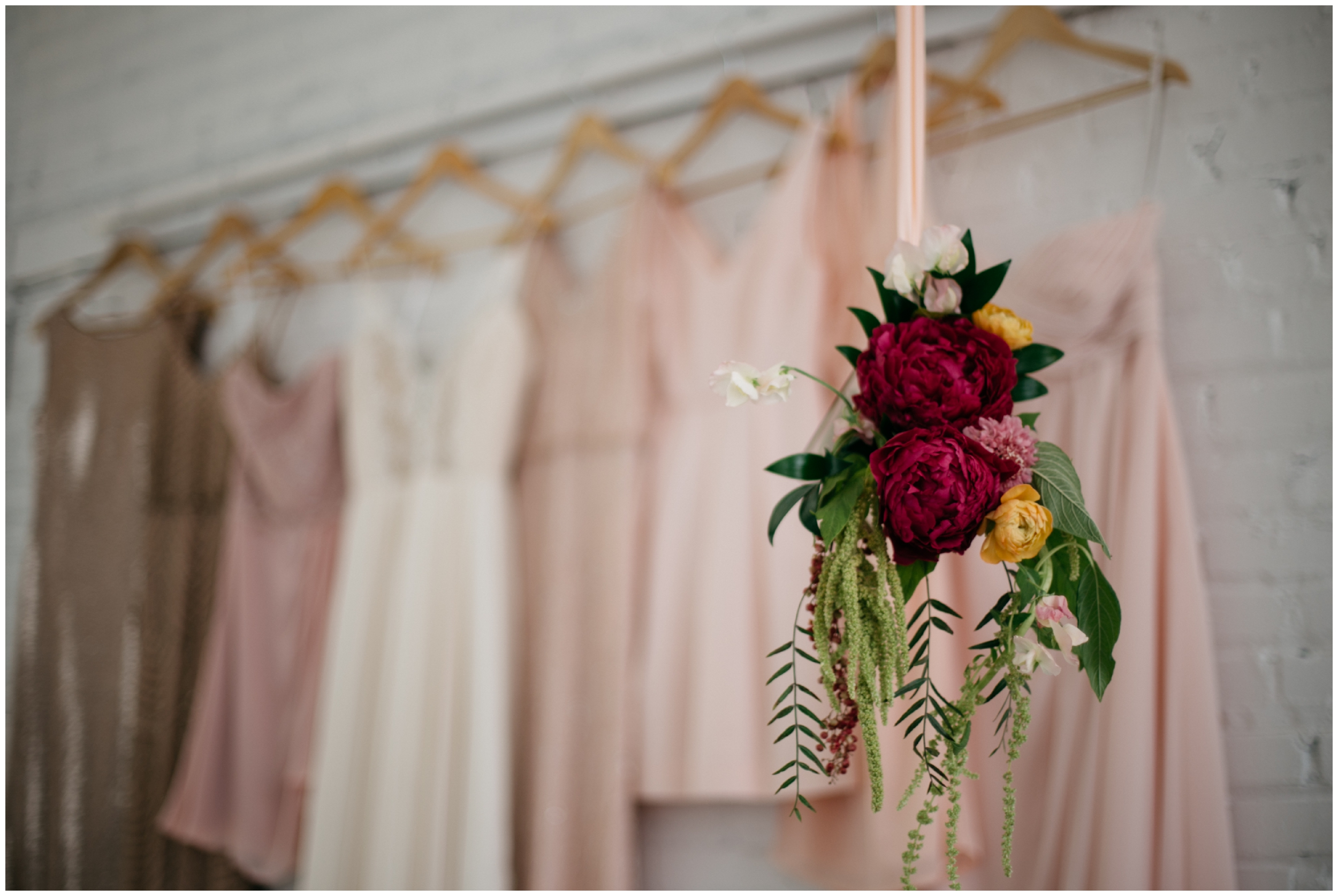 Mismatched blush colored bridesmaids dresses hanging in the bridal suite at the NP Event Space
