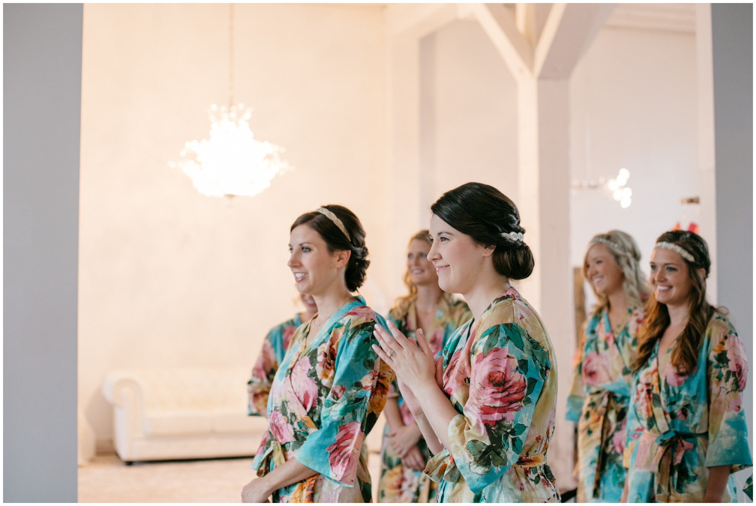 Emotional bridesmaids in floral robes watching bride get into her wedding dress at the NP Event Space
