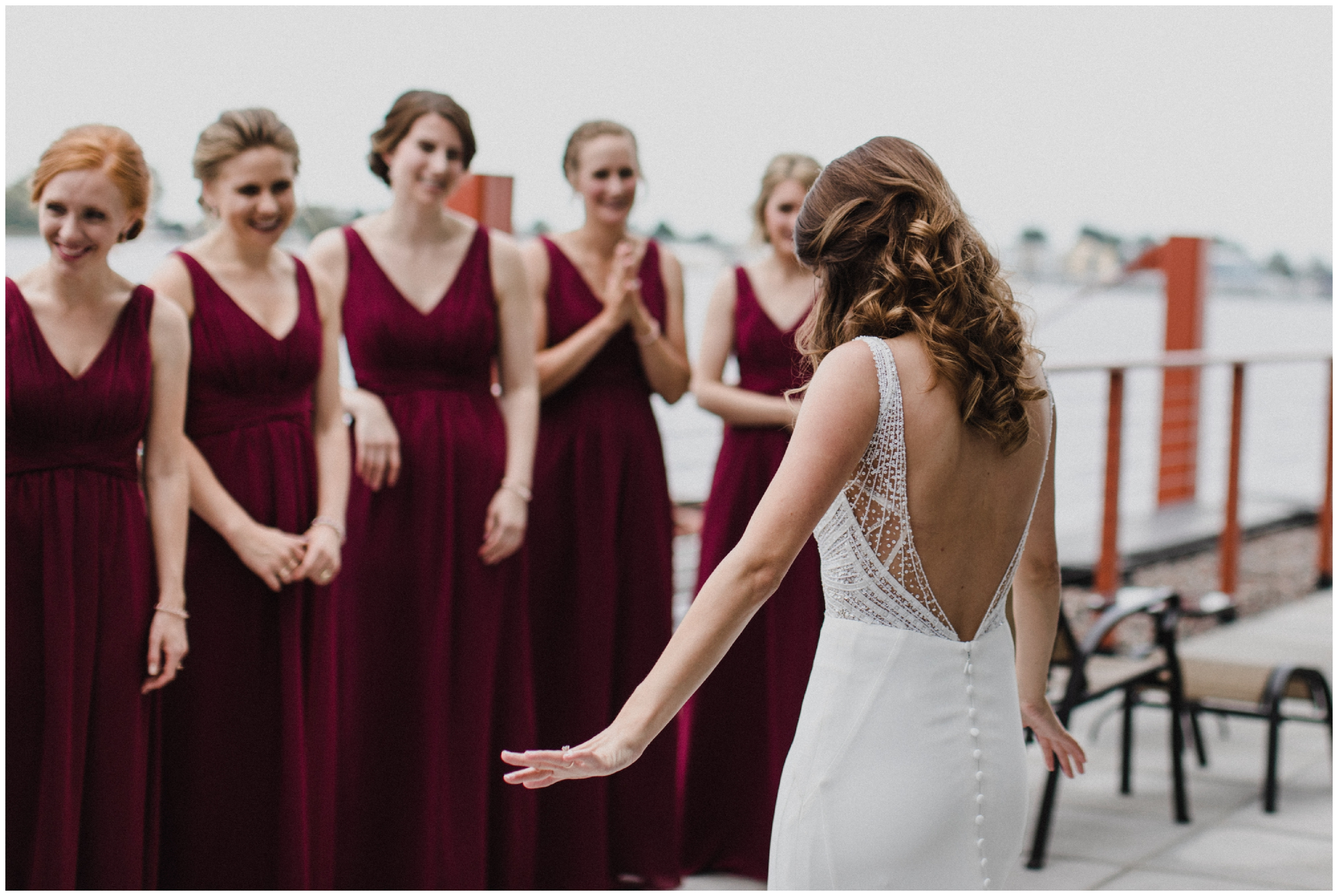 Bride's dress reveal with bridesmaids on the shore of lake Superior