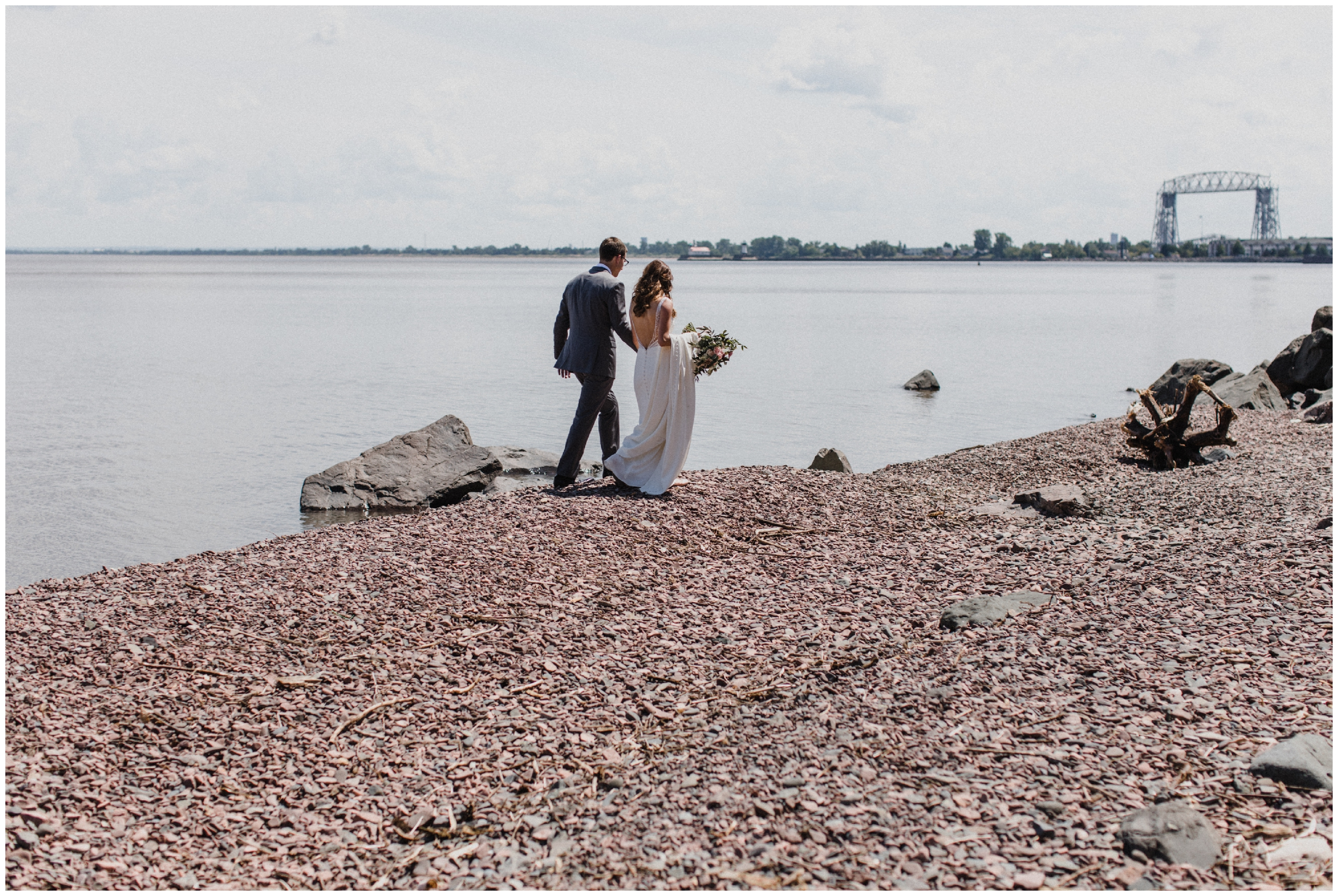 Bride and groom on rocky shore of lake superior