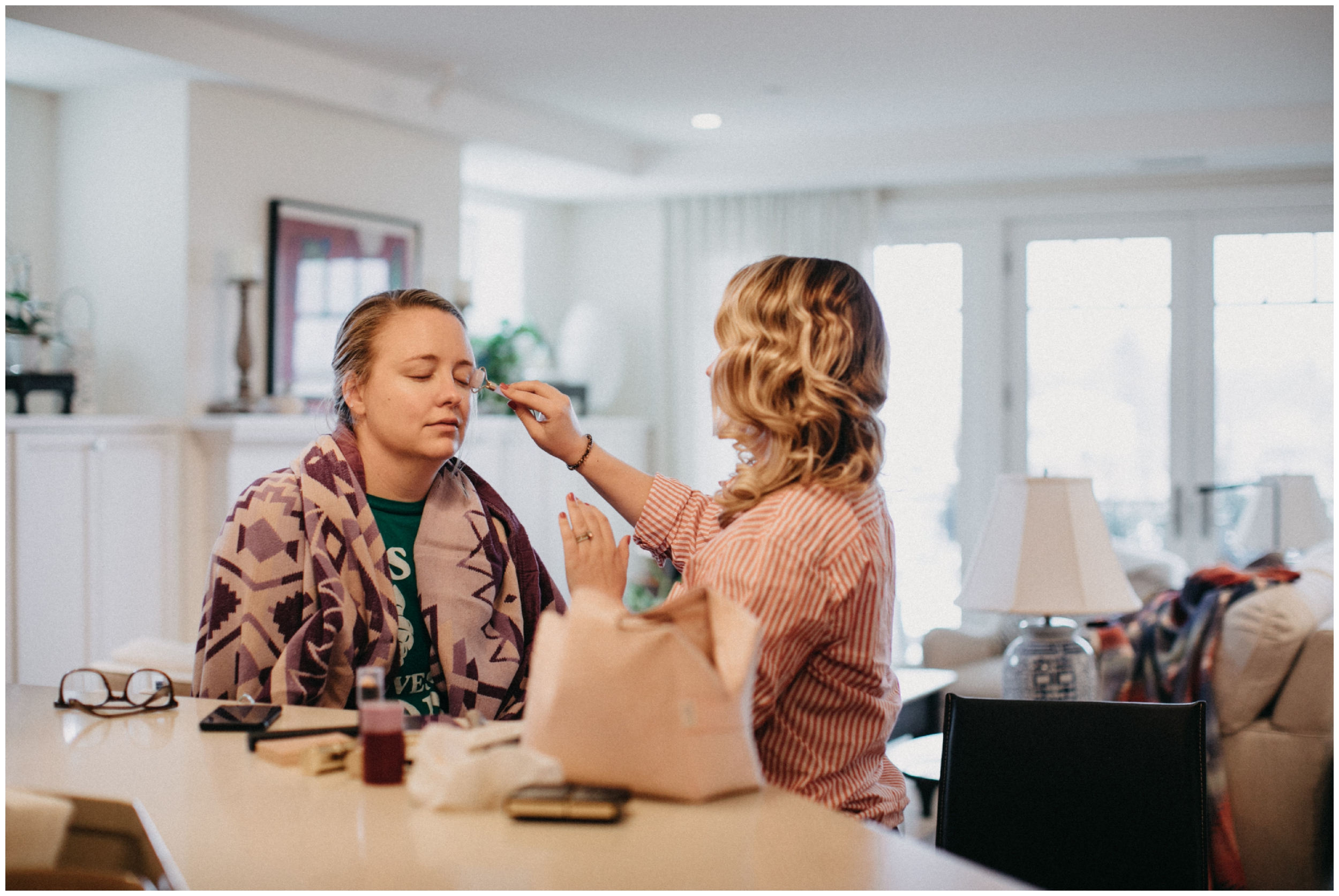 Sister helping bride put on her make-up for wedding at Paikka