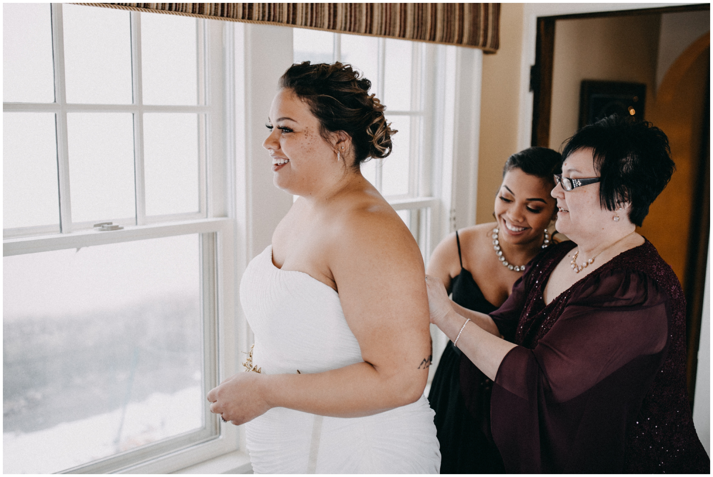 Mother and sister of the bride helping her into wedding dress in Minneapolis Minnesota