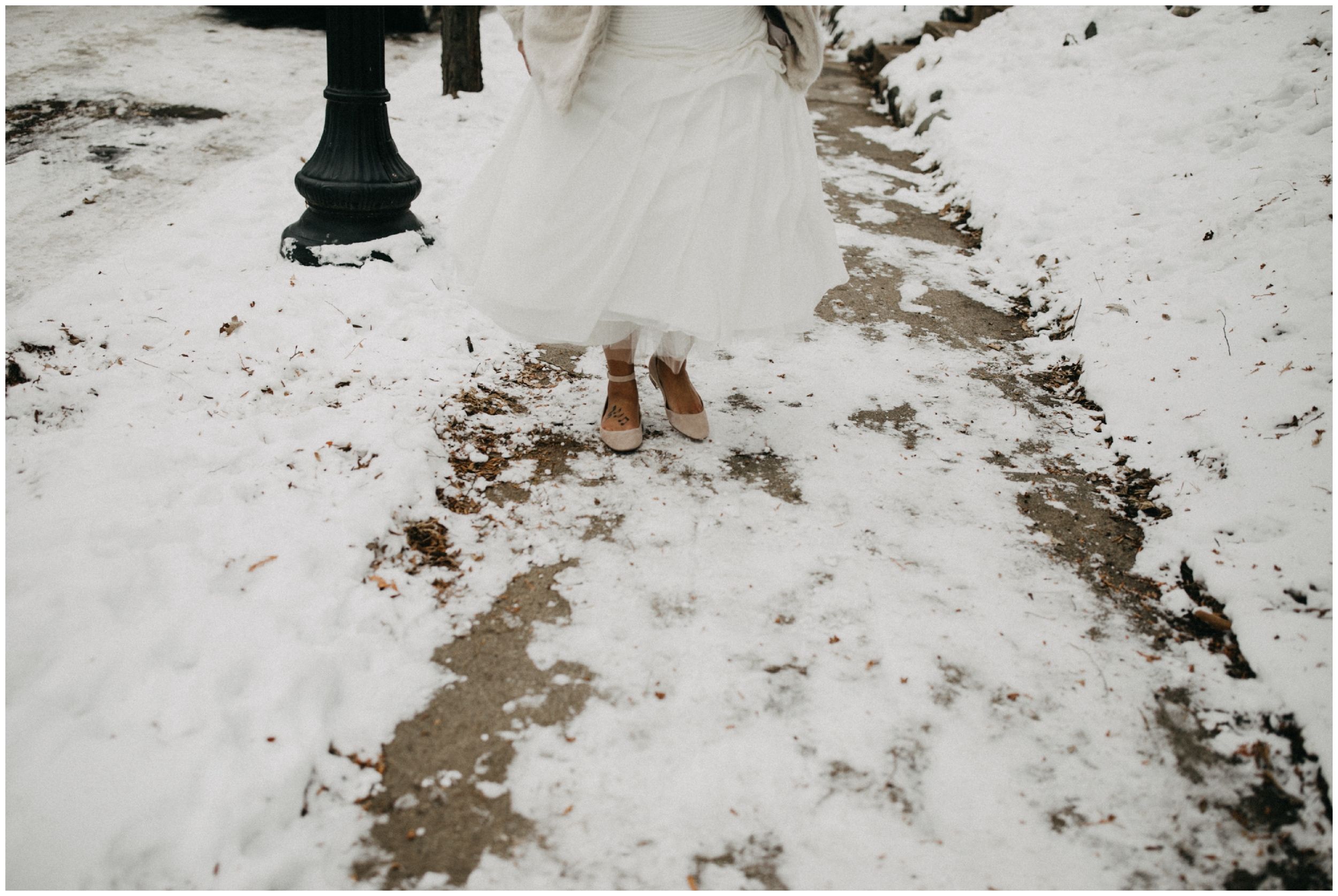 Bride walking down snow covered side walk in Minneapolis Minnesota