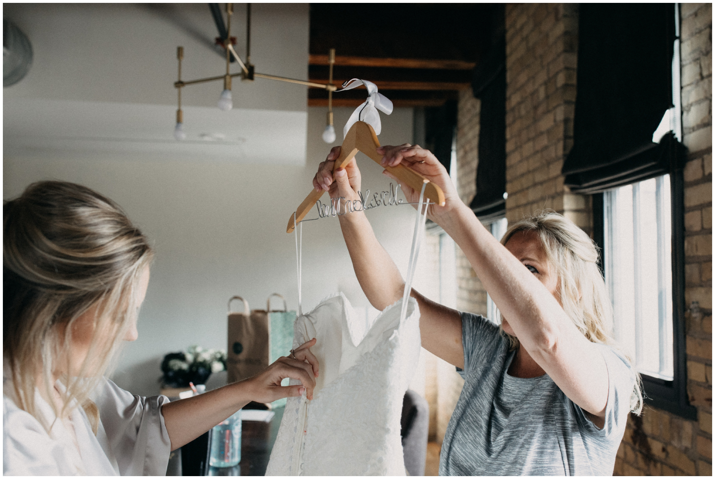 Mother of bride helping her into wedding dress at the Hewing Hotel in Minneapolis