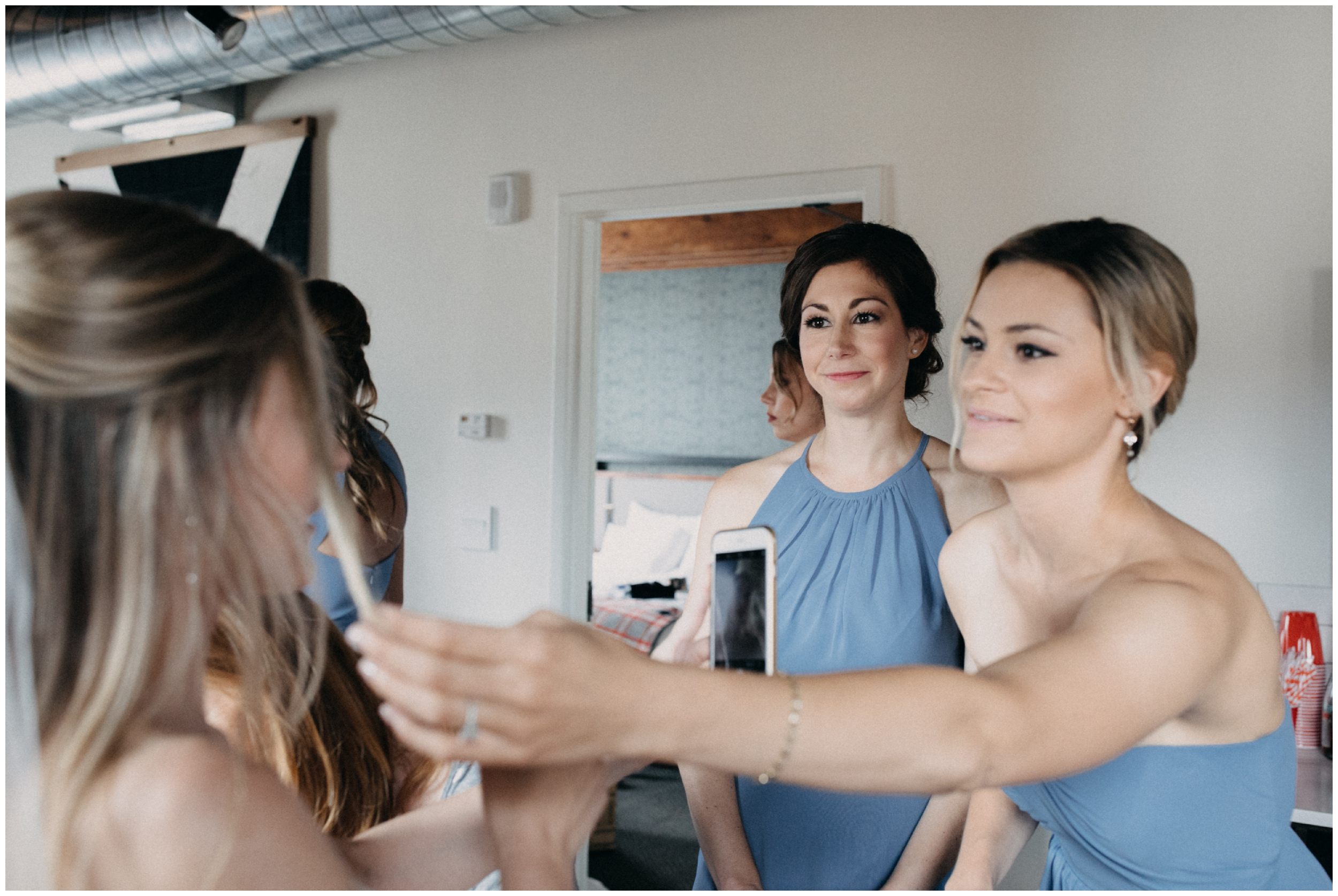 Bridesmaids helping bride get ready for wedding day at the Hewing Hotel in Minneapolis