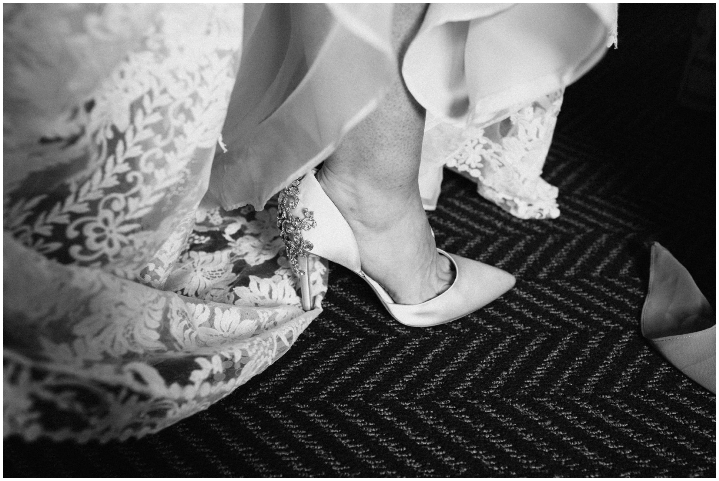 Bride putting on Badgley Mischka wedding heels at the Hewing Hotel in Minneapolis, MN