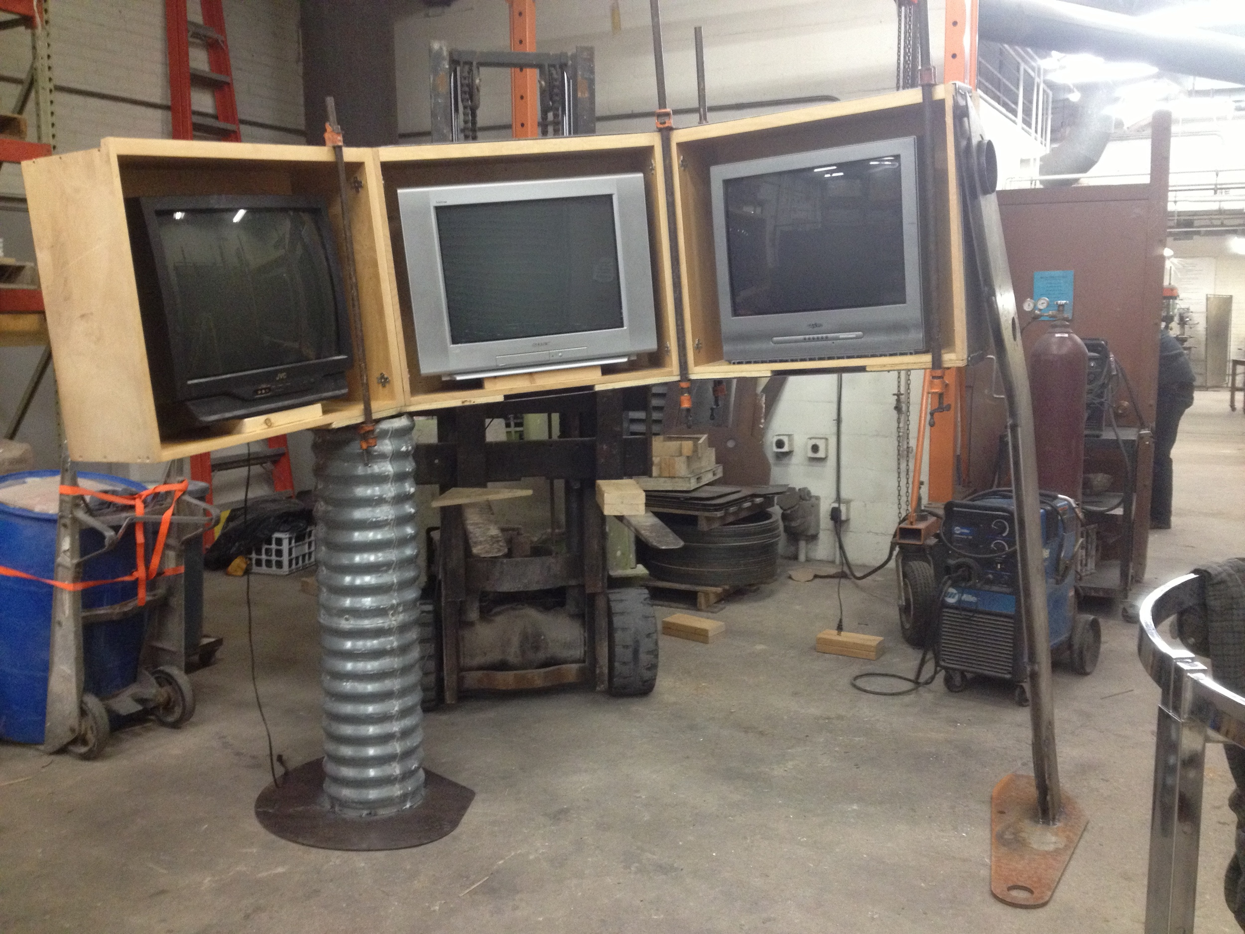 The monitors mounted in their boxes and raised on their support columns. At this point everything is being held in place by gravity, while the pipe clamps here are serving the function of holding the ribbed columnar element and metal sheafing in place, prior to being bolted and screwed together. In the final product the clamps serve as an aesthetic device.