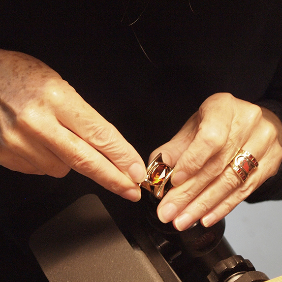 The final step in bezel setting a  stone is called bright cutting, where a very sharp instrument called a graver cuts a sliver of gold away from the very top of the bezel.