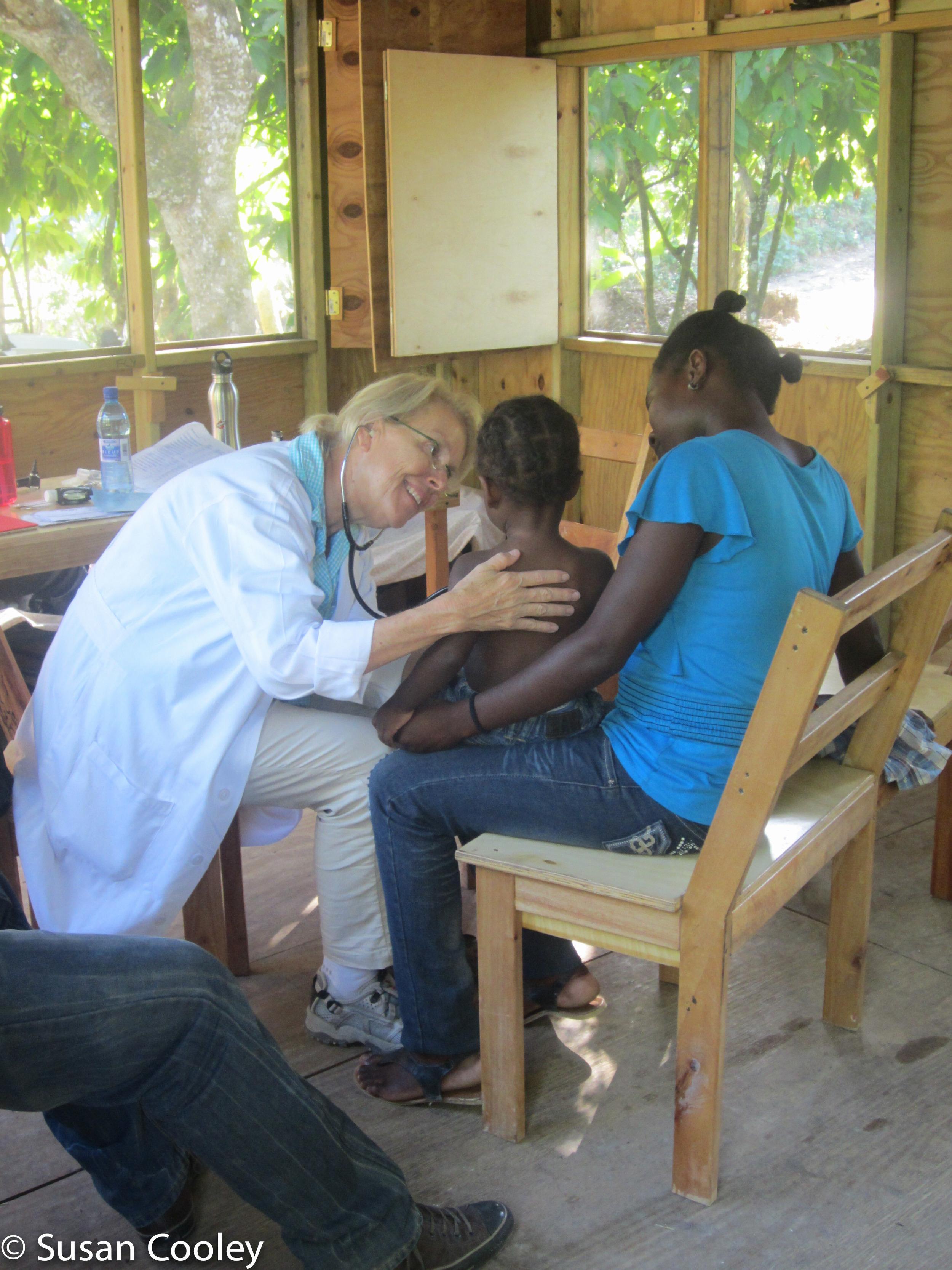 Susan examines clinic patient, 2013.