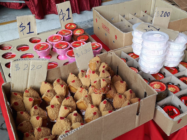 Brown cupcakes 'huat kuey' in Hokkien are offered to the deceased. 'Niangao' round cakes with red labels on them.
