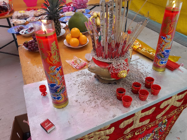 A joss table with small cups of wine and tea. Three sticks of incense must be lit when making prayers.