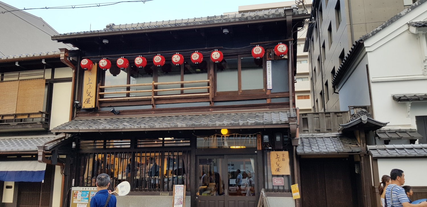 A narrow 'machiya' shophouse in Kyoto with a 'kura' storehouse on the right side.
