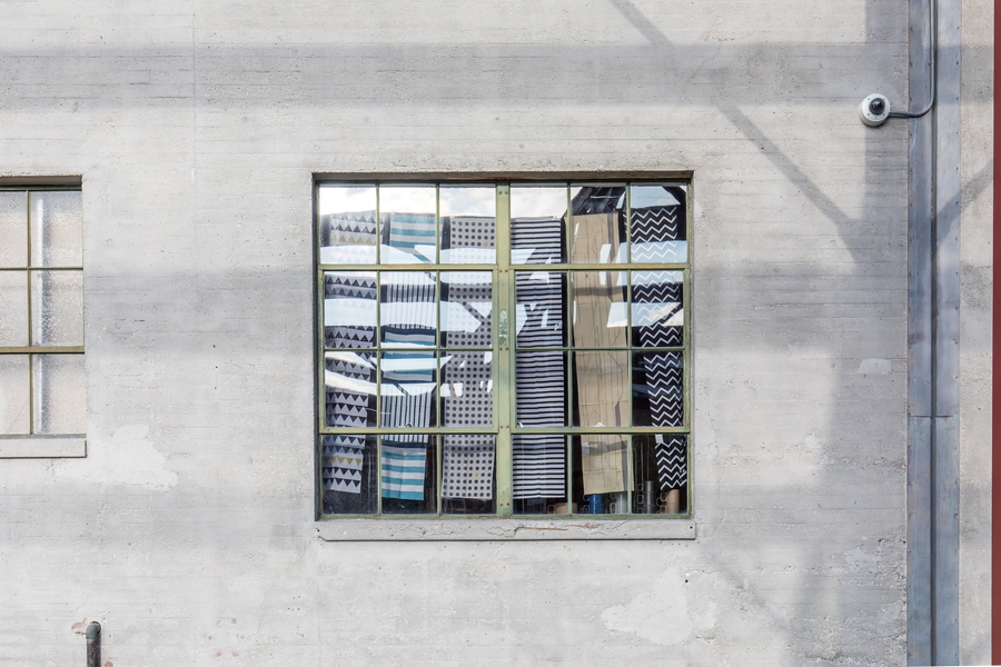 入り口横の窓から、中に吊るされた手ぬぐいが見えます。 まるで、お洒落なブラインドのようですね。
