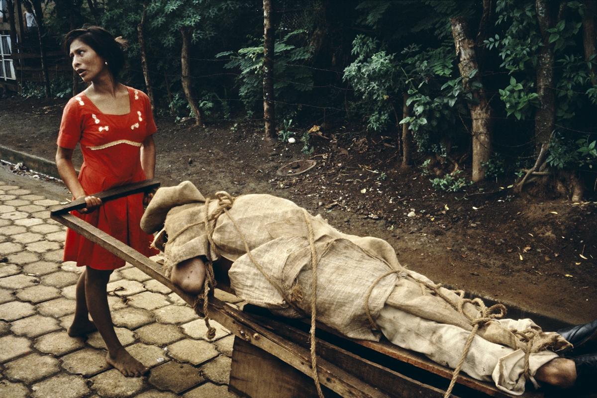মনিম্বো নারী তার স্বামীকে কবর দেবার জন্য বাড়ীর পেছনের উঠানে নিয়ে যাচ্ছে। নিকারাগুয়া ১৯৭৯। ছবি সুজান ম্যাইসিলাস। ম্যাগনাম ফটোস।