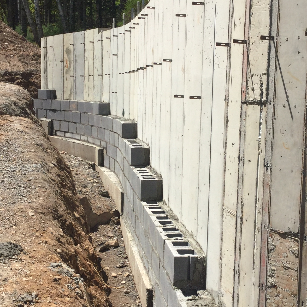 """A poured in place concrete wall prepped to receive a """"decorative"""" natural stone facing."""