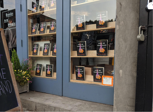 The window fronts at Books Are Magic decorated with Megan Abbott's new novel, Give Me Your Hand.