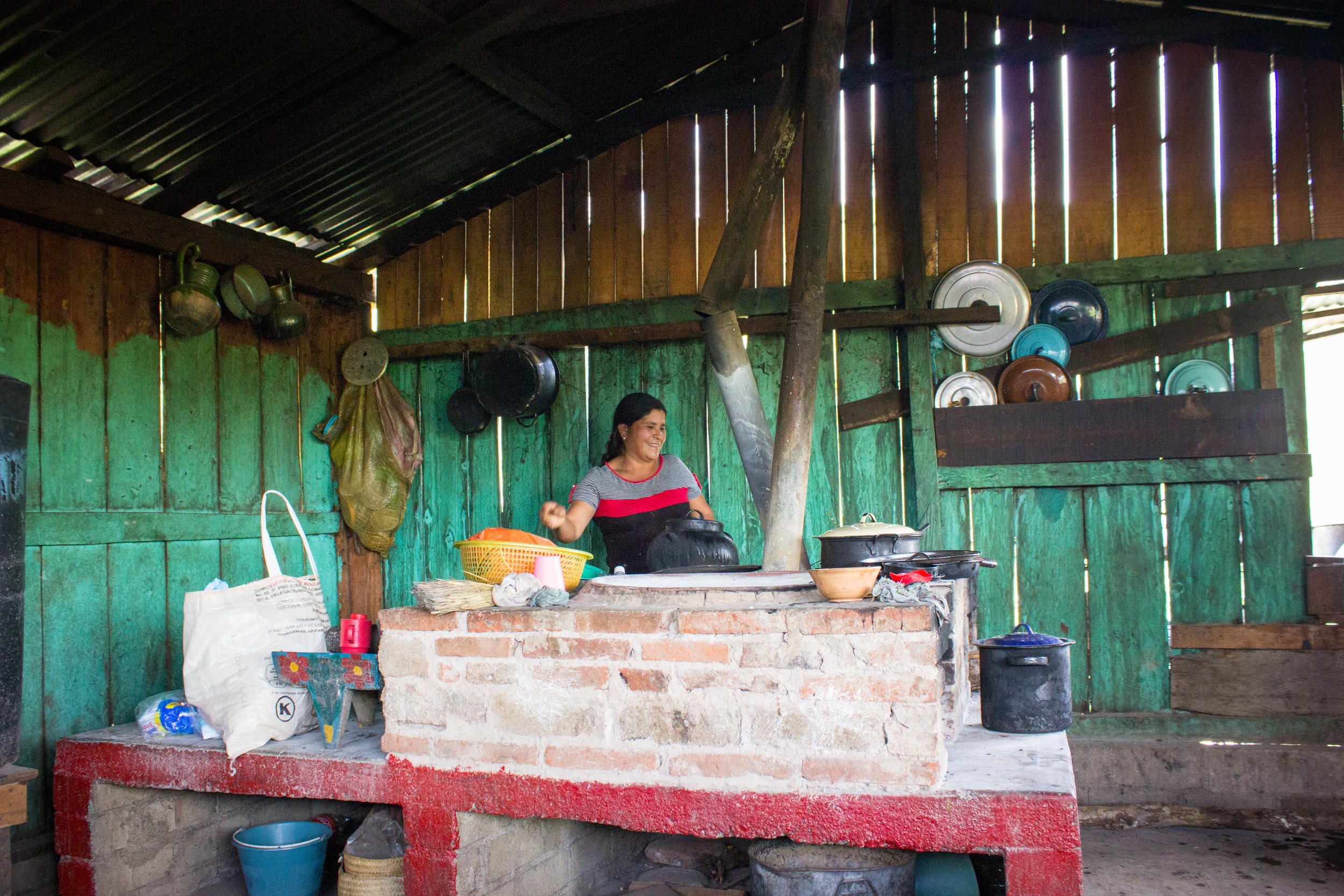 A neighbor in her kitchen, making a luncheon for all of us. In the villages, women cook over open fires in rooms separate from the homes.