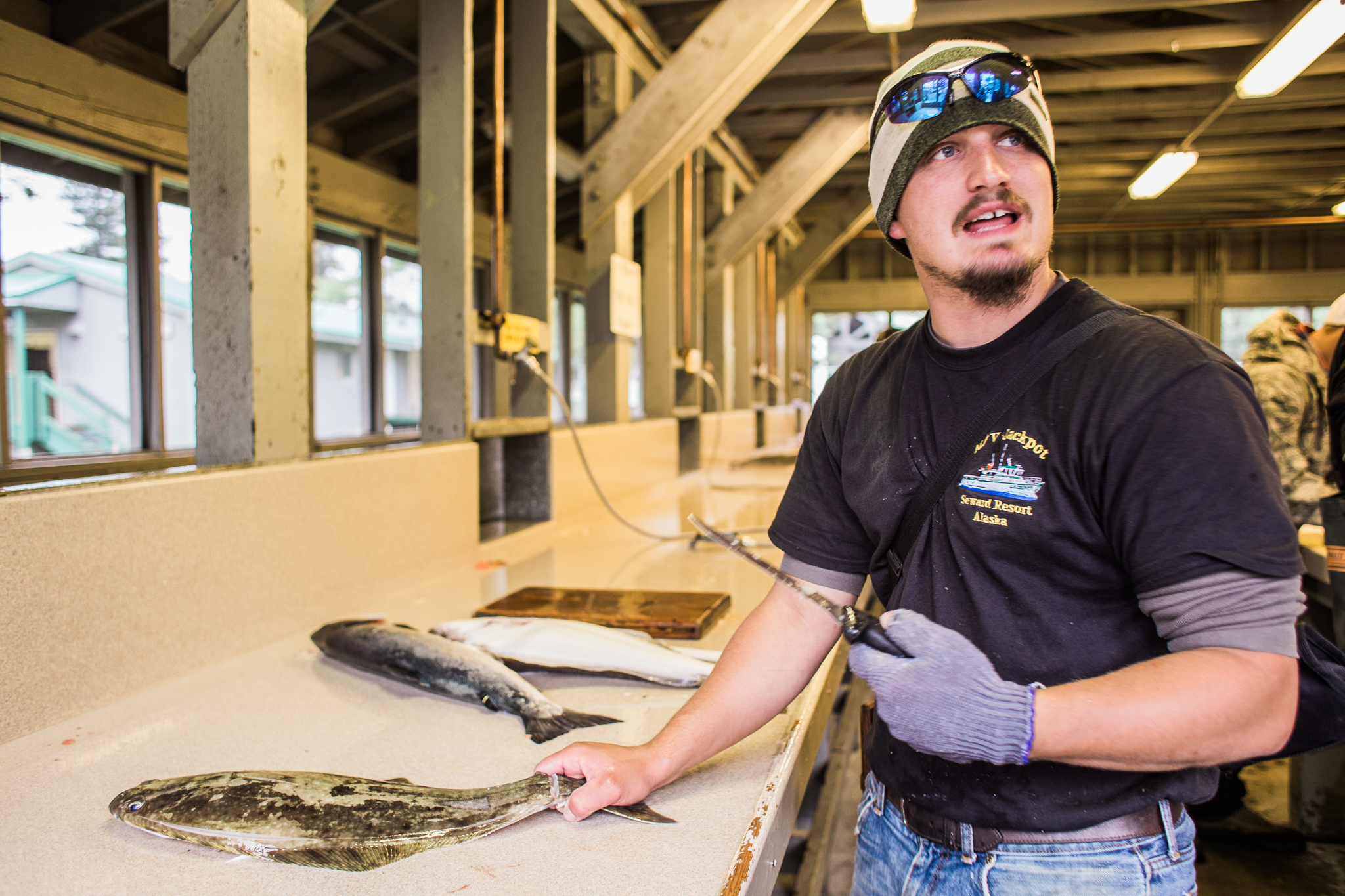 Here, Benjamin is filleting his customer's fish at the Seward Military Resort.
