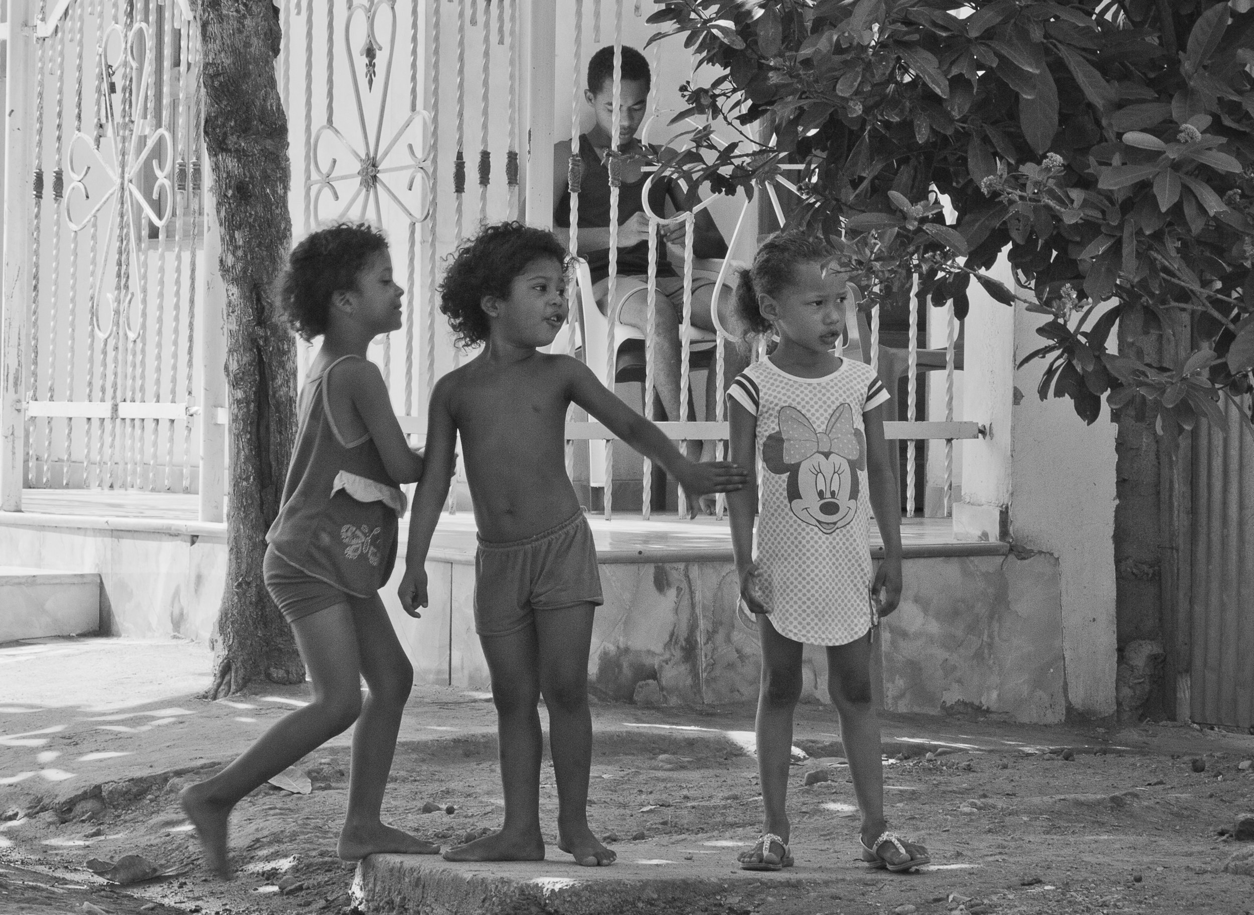 In this image girls are playing in front of a re-contructed house, they represent the vigorous life of the emerging town after fourteen years of rebuilding done step by step by the demanding enterprise of their parents work.