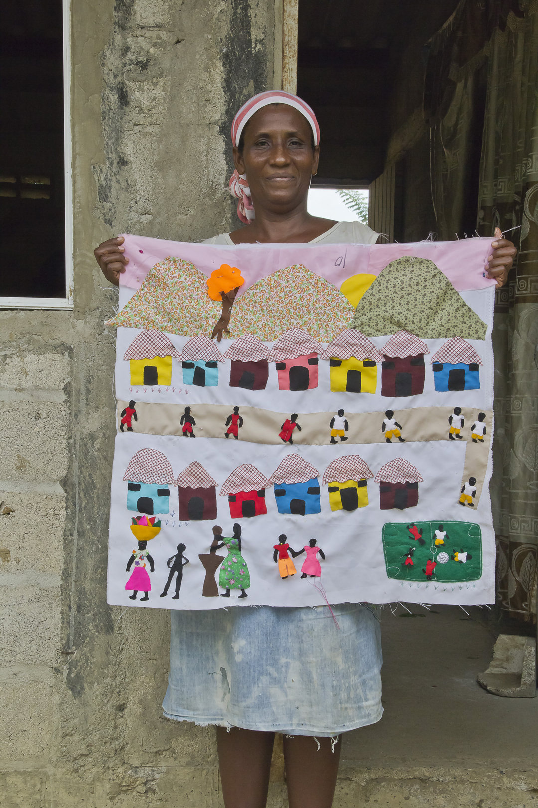 Here a woman is showing her woven fabric artwork representing the idea of community integration, her love for the sports and her attachment to cultural traditions