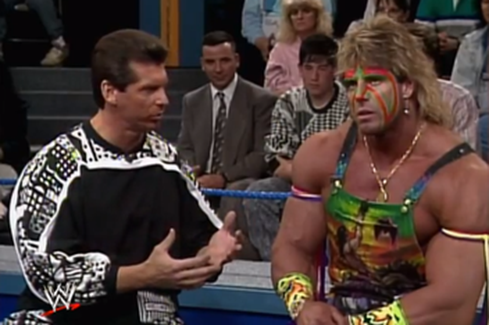 "Vince McMahon and the Ultimate Warrior, circa 1991, on a ""Casual Friday,"" unaware of the fans sitting in attendance during their intense contract negotiation."