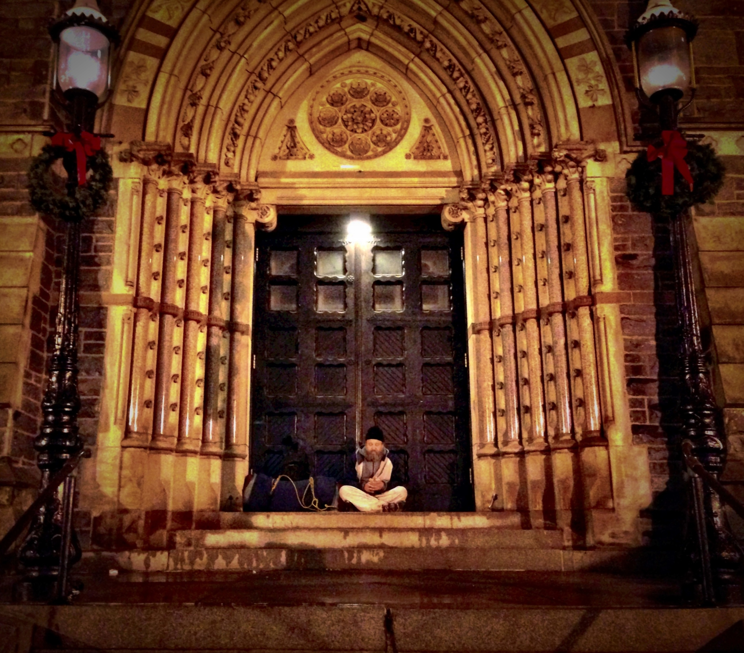 A homeless man sits in a church's archway in Boston on a cold winter night.