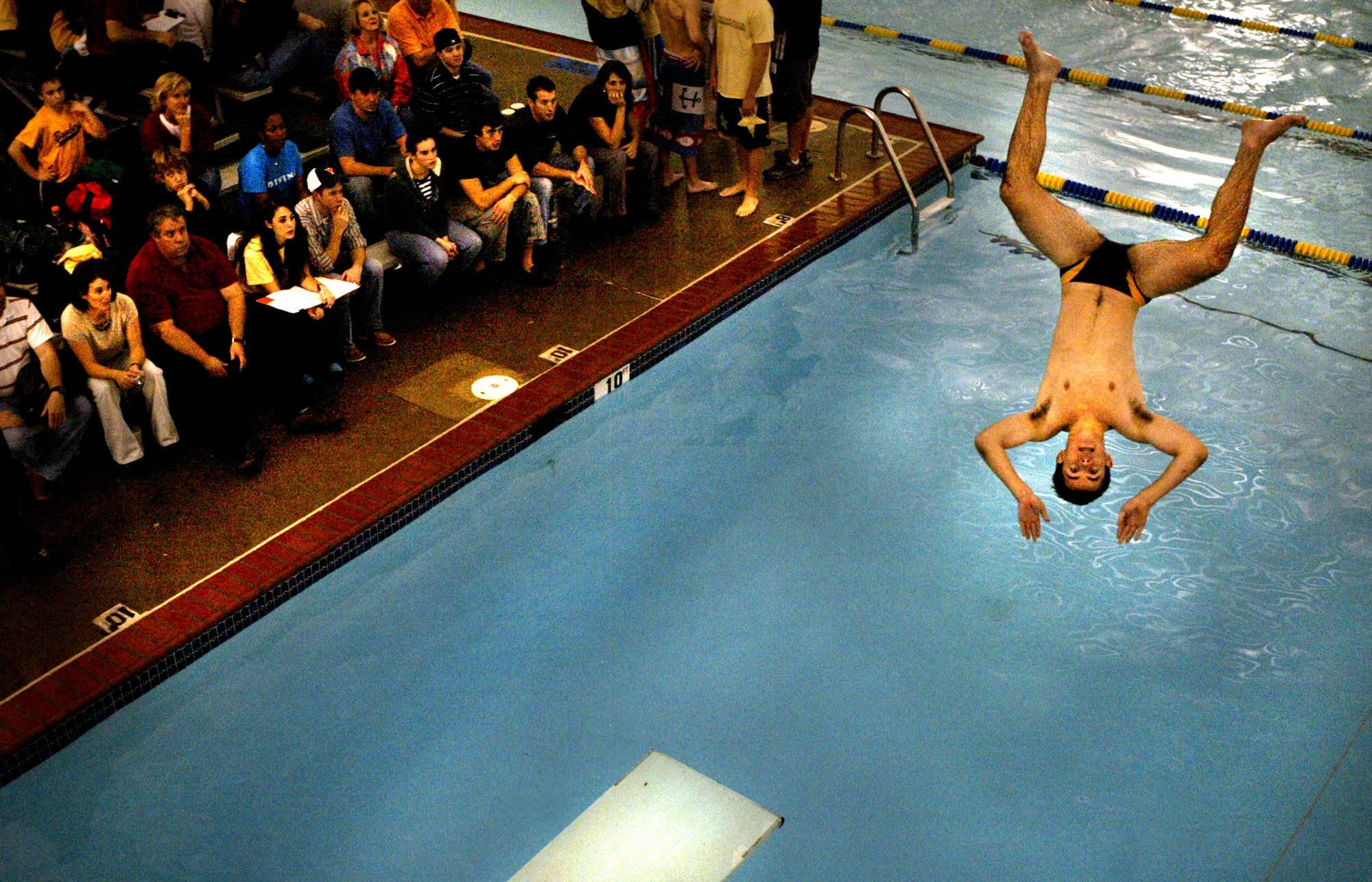 Great Bridge's Conrad Edler performs off of the diving board during their district meet.