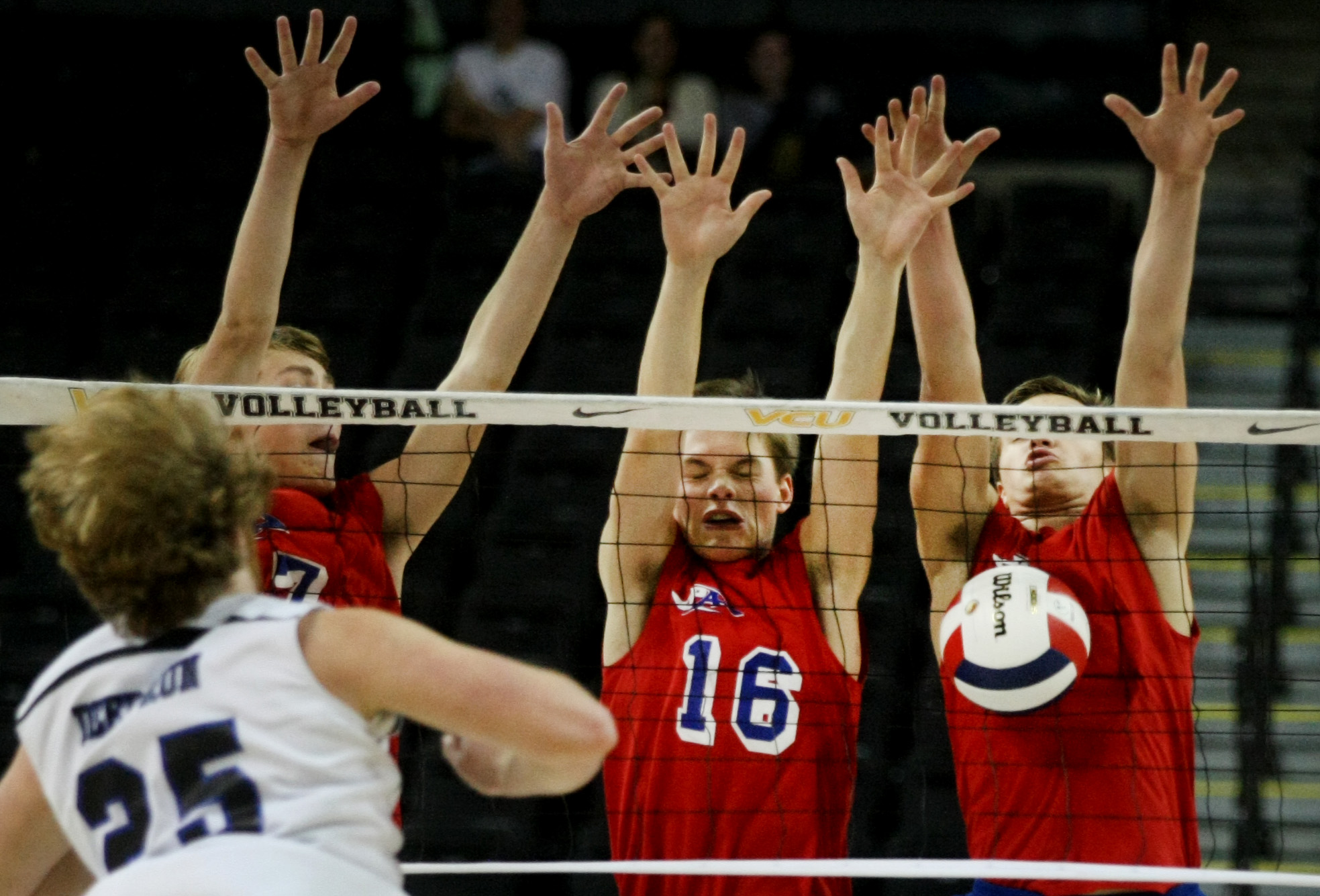 Princess Anne's Courtland Scharenborg, background left, Andrew Butler, center and Chase Howard attack the net on a shot by Deep Run's Craig Nelms during their win to claim the Group 5A boys volleyball state championship, Friday, Nov. 21, 2014 at the Siegel Center in Richmond.  (Jason Hirschfeld   For The Virginian-Pilot)