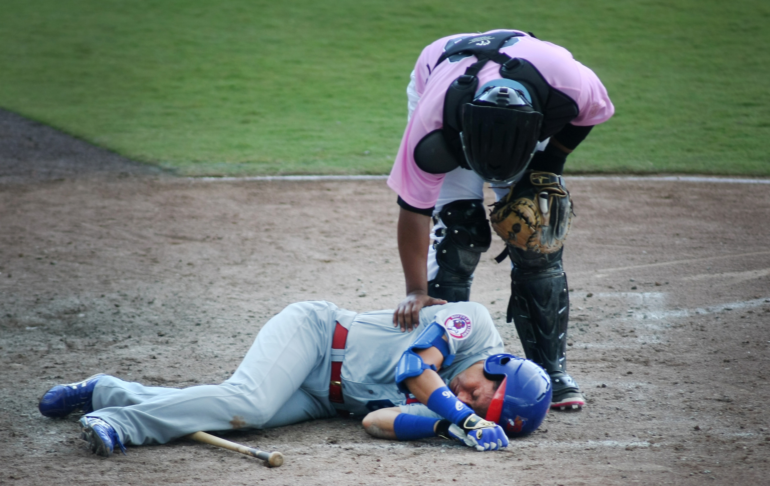 Tides catcher Audry Perez tends to Buffalo's Munenori Kawasaki as he laysmotionless after getting drilled in the head with a fastball in the top of the seventh inning. Kawasaki remained on the ground for several minutes but was then helped off the field, Sunday, May 10, 2015 at Harbor Park in Norfolk.