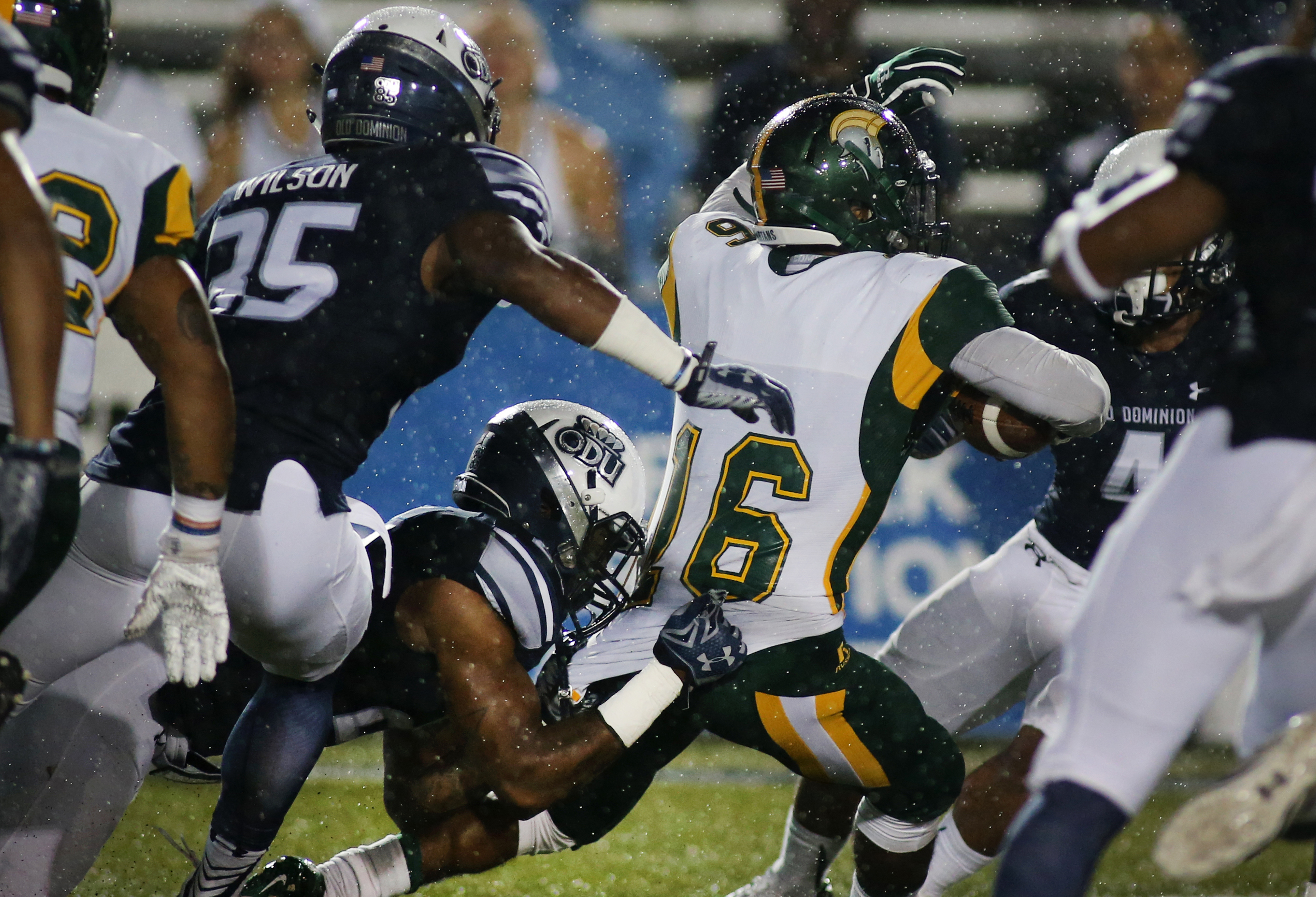 Old Dominion's Fellonte Misher, center below, brings down Norfolk State's Donté Haynesworth late in the third quarter, Saturday, Sept. 12, 2015 at Foreman Field in Norfolk.