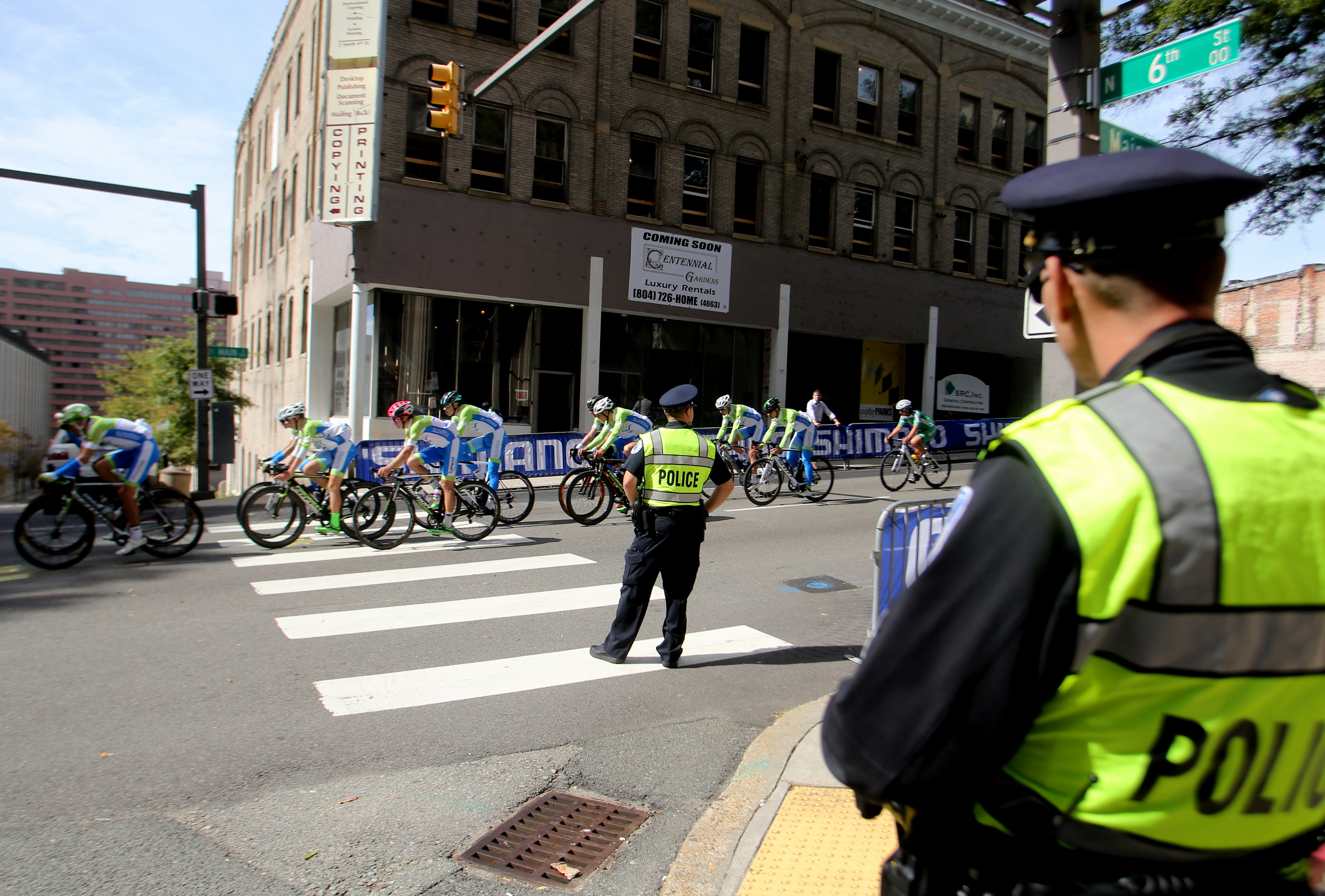 Police keep a watchful eye as riders pass by during the Road Circuit Training portion of the UCI Road World Championships cycling races in Richmond, Va., Thursday, Sept. 24, 2015.  (AP Photo/Jason Hirschfeld)