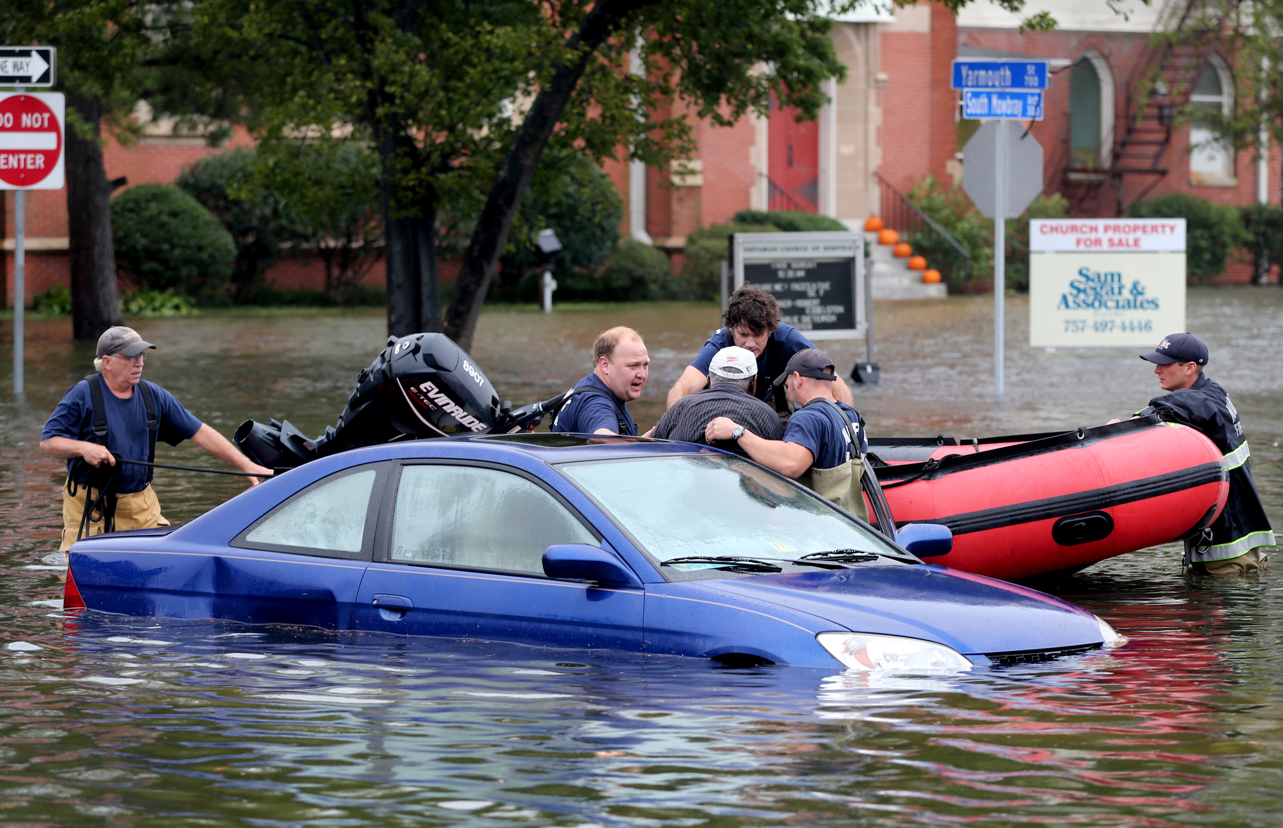 Members of Norfolk Fire-Rescue pull a man from his car that was stranded due to flooding, Sunday, Oct. 4, 2015 in Norfolk, Va.     (AP Photo/Jason Hirschfeld)