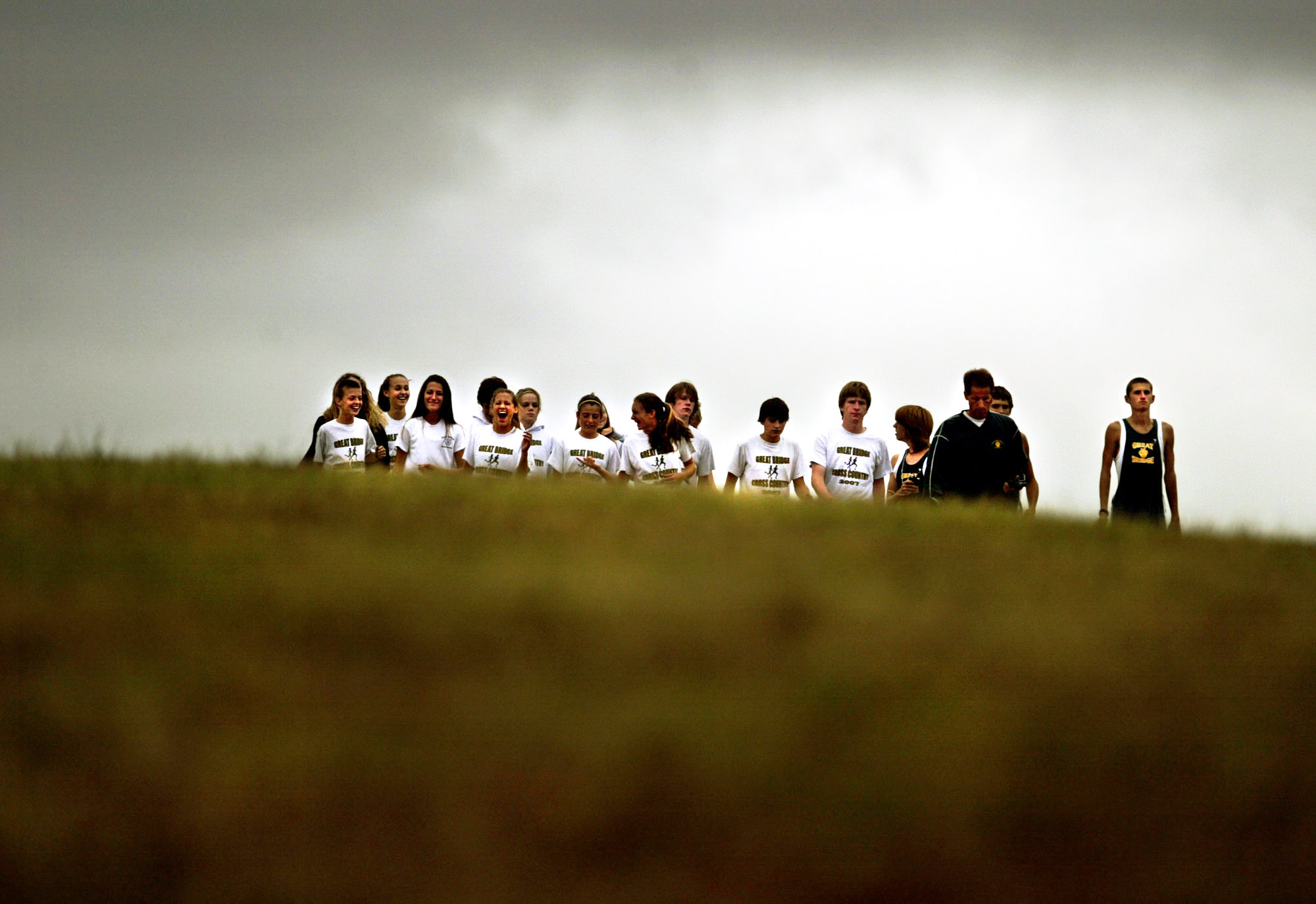 The Great Bridge Cross Country team emerges from the top of a hill before the start of a meet.