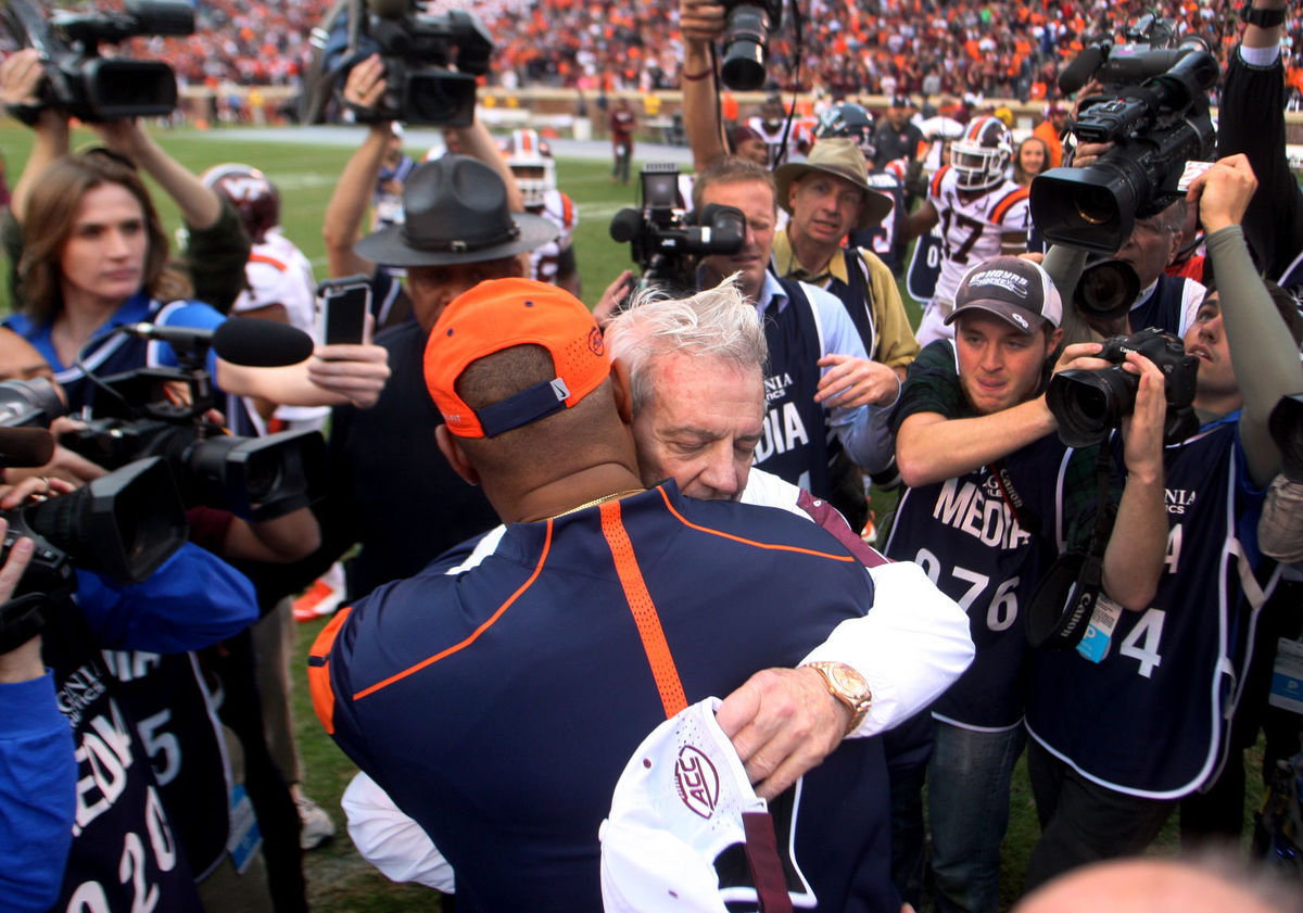 Virginia Tech head football coach Frank Beamer and University of Virginia coach Mike London embrace at midfield after the Hokie's beat the Cavaliers 23-20, Saturday, Nov. 15, 2015 in Charlottesville in what would be Beamer's last game with the in-state rivals as he retired at the end of the season.