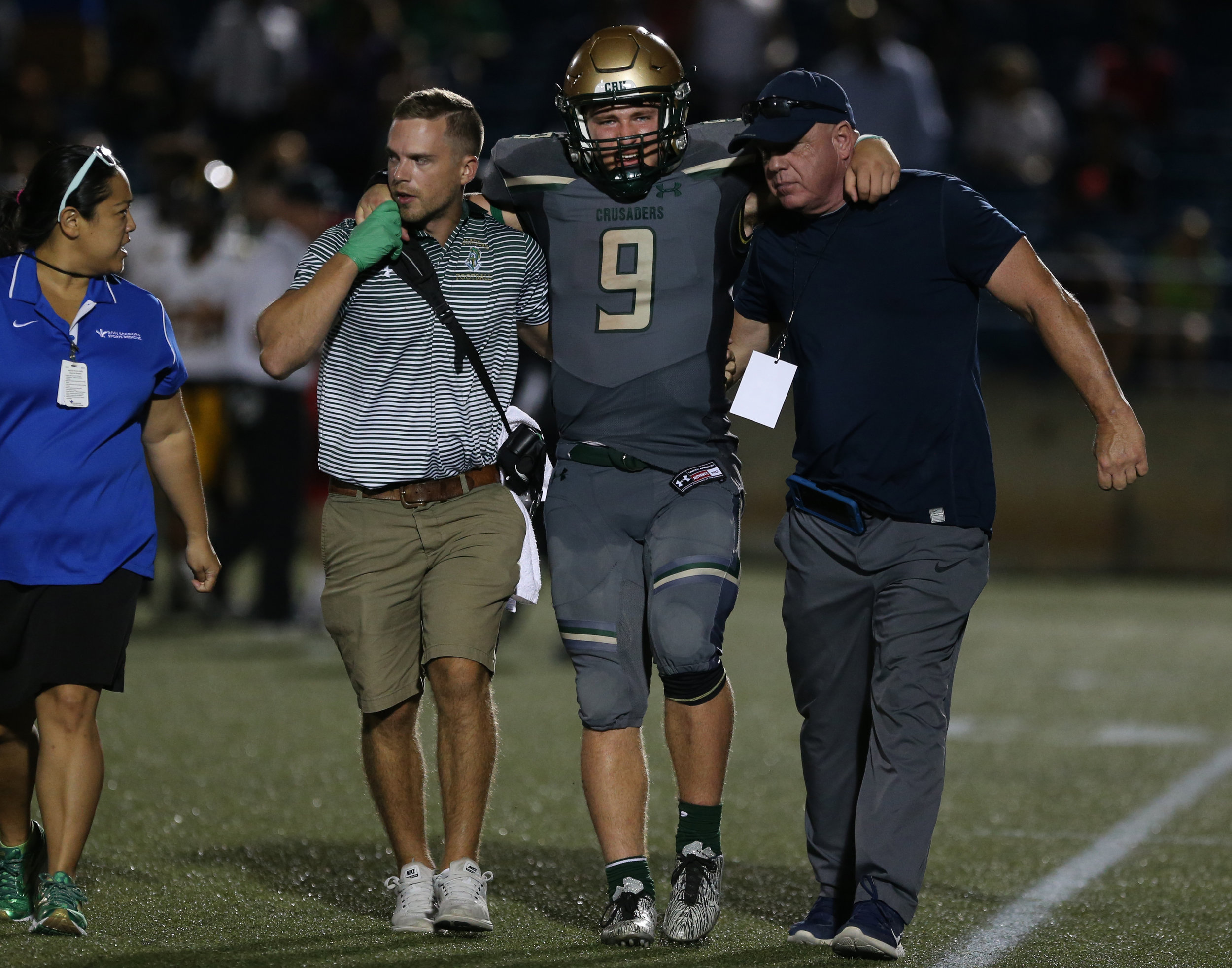 Bishop Sullivan's Jake Low is helped off the field after an injury  during the Crusaders' 14-7 loss, Saturday, August 26, 2017 at the Sportsplex in Virginia Beach.
