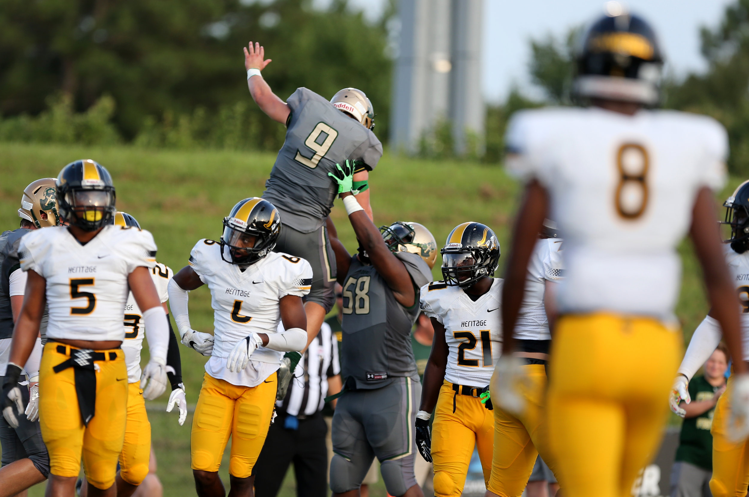 Bishop Sullivan's Jake Low is raised in the air by teammate Altrique Barlow after Low scored a touchdown against American Heritage during the Crusaders' 14-7 loss, Saturday, August 26, 2017 at the Sportsplex in Virginia Beach.
