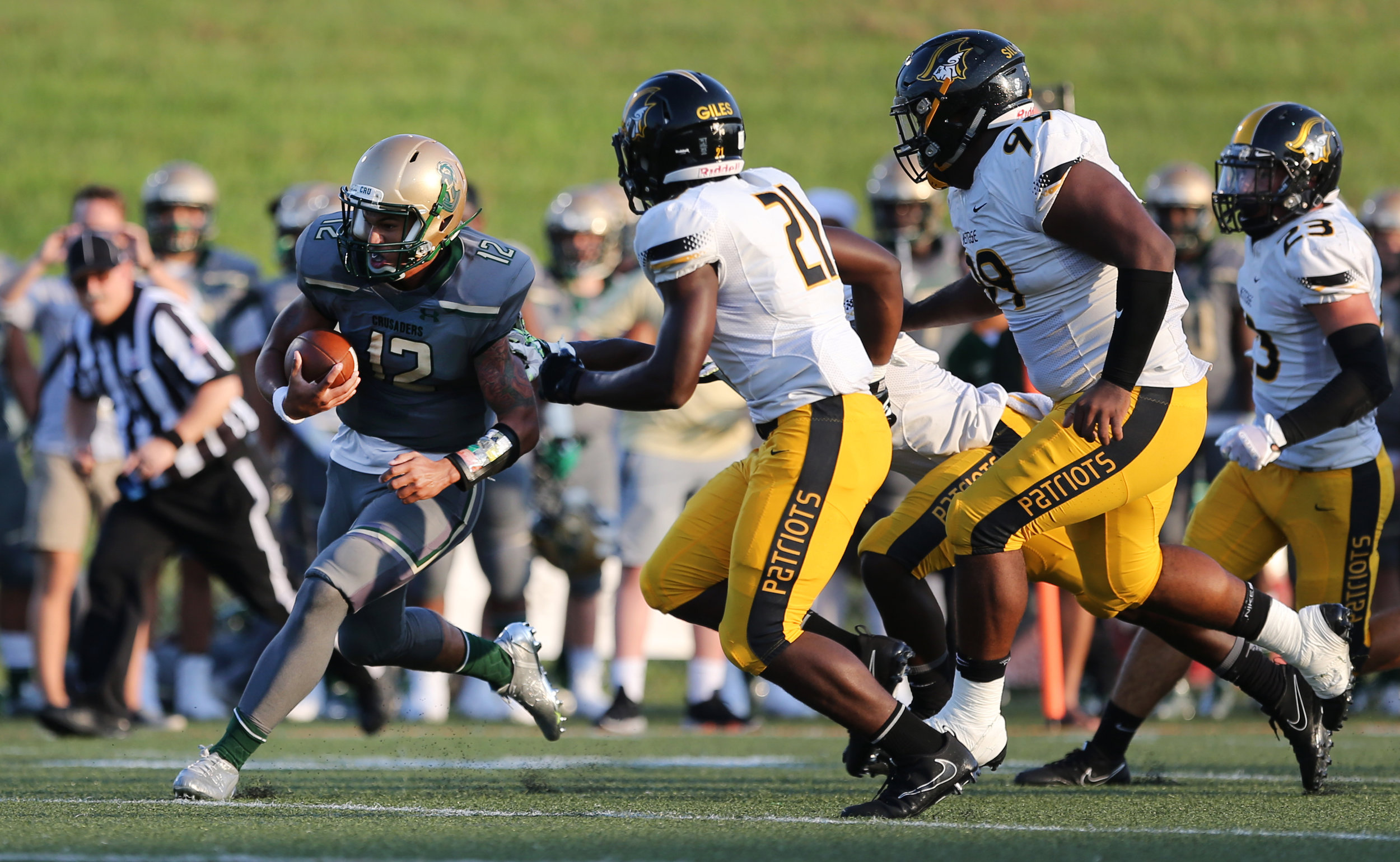 Bishop Sullivan's Tyler DeSue runs the ball on a quarterback keeper play past American Heritage defenders  during the Crusaders' 14-7 loss, Saturday, August 26, 2017 at the Sportsplex in Virginia Beach.