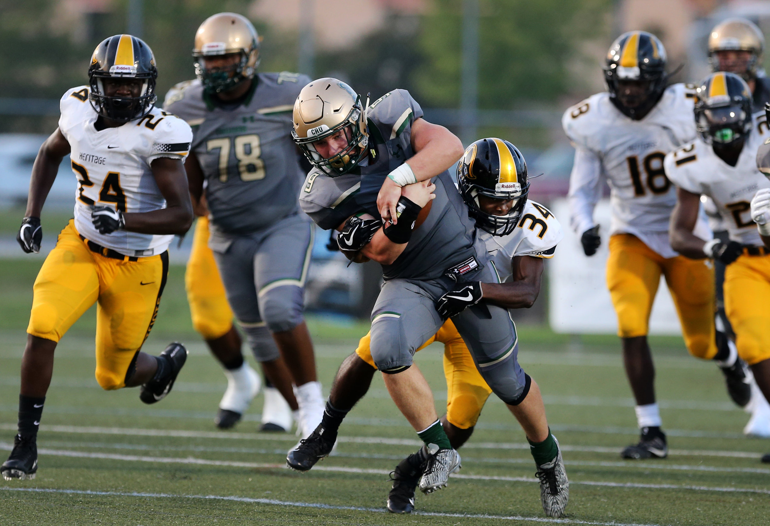 Bishop Sullivan's Jake Low runs for a first down before being tackled by American Heritage's Clarence Burley during the Crusaders' 14-7 loss, Saturday, August 26, 2017 at the Sportsplex in Virginia Beach.